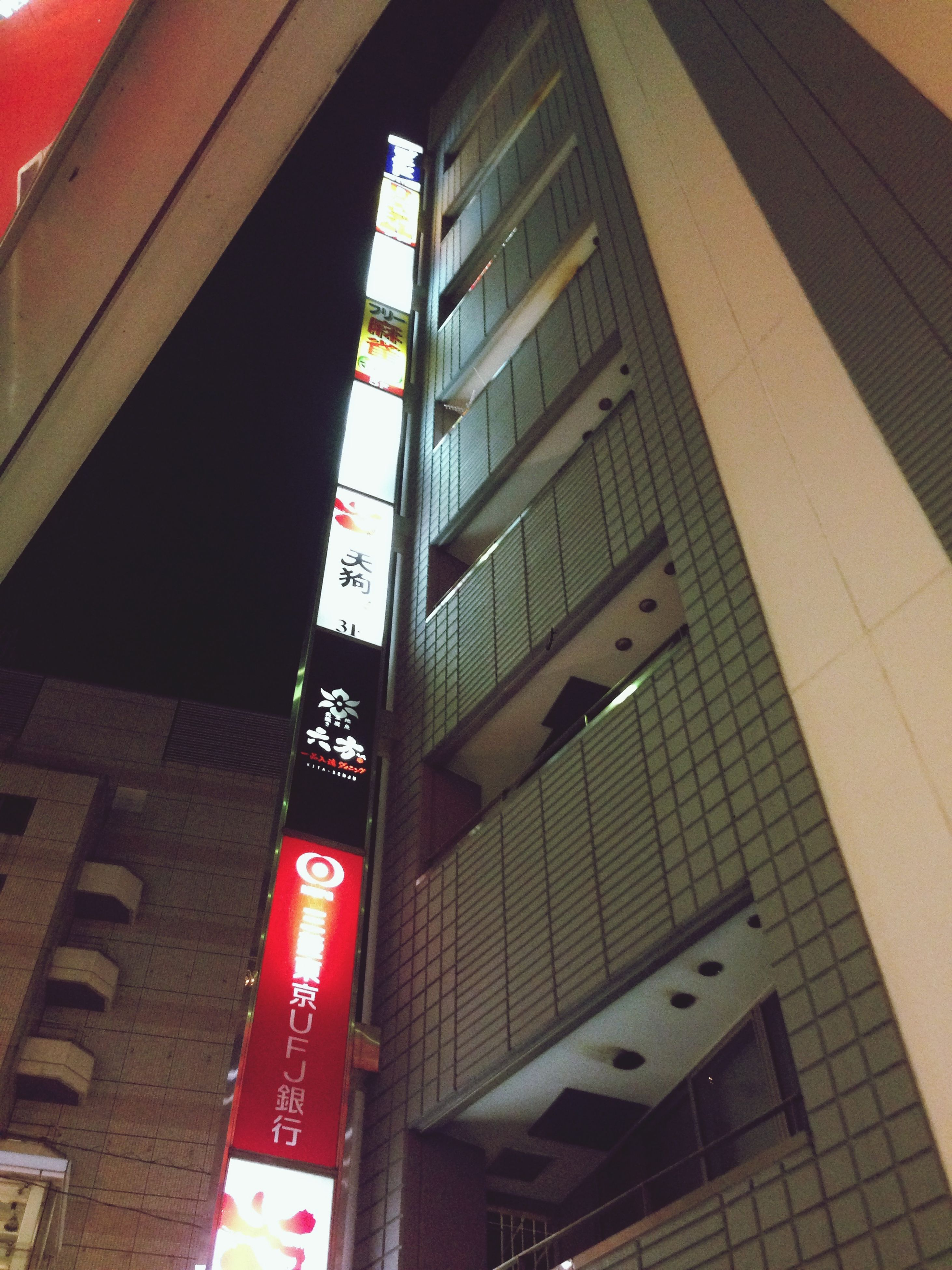 architecture, building exterior, built structure, low angle view, city, illuminated, building, text, night, city life, residential building, communication, modern, outdoors, no people, residential structure, lighting equipment, tall - high, red, office building