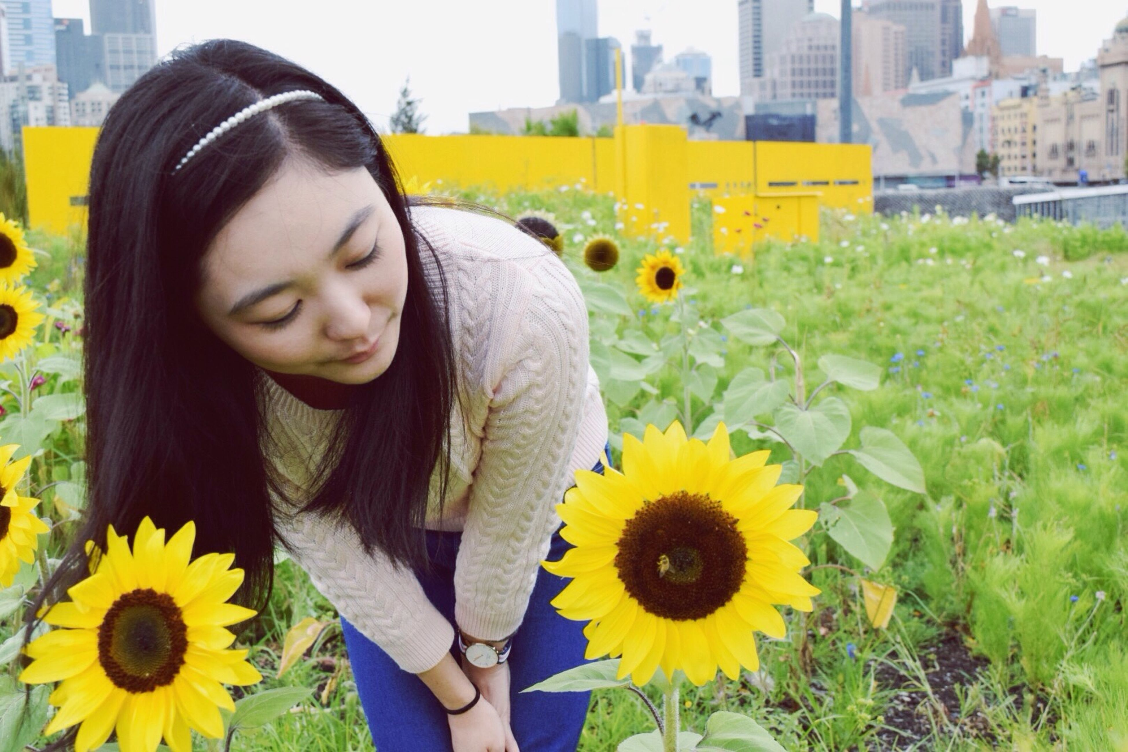 yellow, flower, person, young adult, lifestyles, casual clothing, freshness, smiling, leisure activity, young women, focus on foreground, waist up, fragility, field, growth, portrait, plant, front view