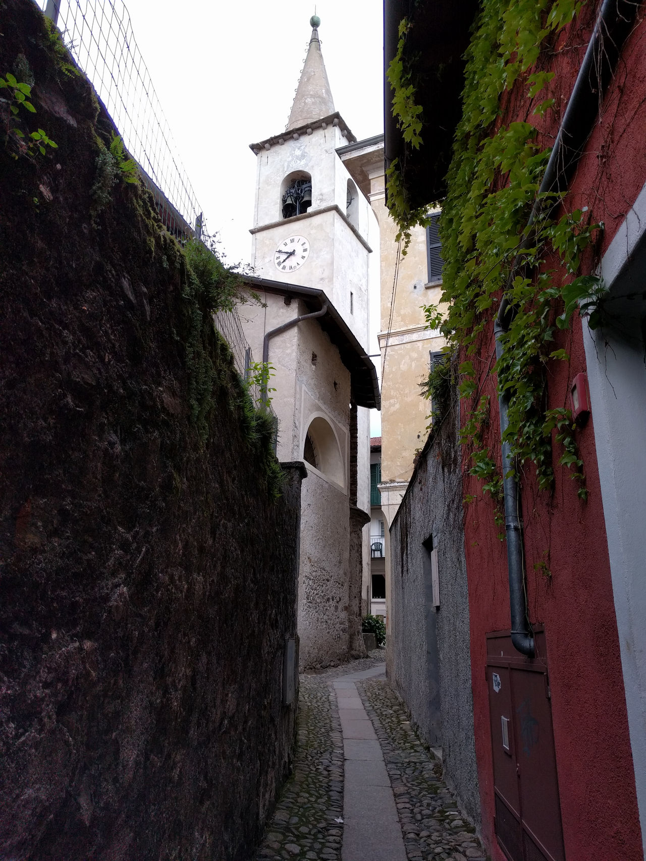 Alley Architecture Building Building Exterior Built Structure Church Day Diminishing Perspective Growth Narrow No People Outdoors Residential Building Residential Structure Sky The Way Forward Town Tree Vanishing Point Walkway