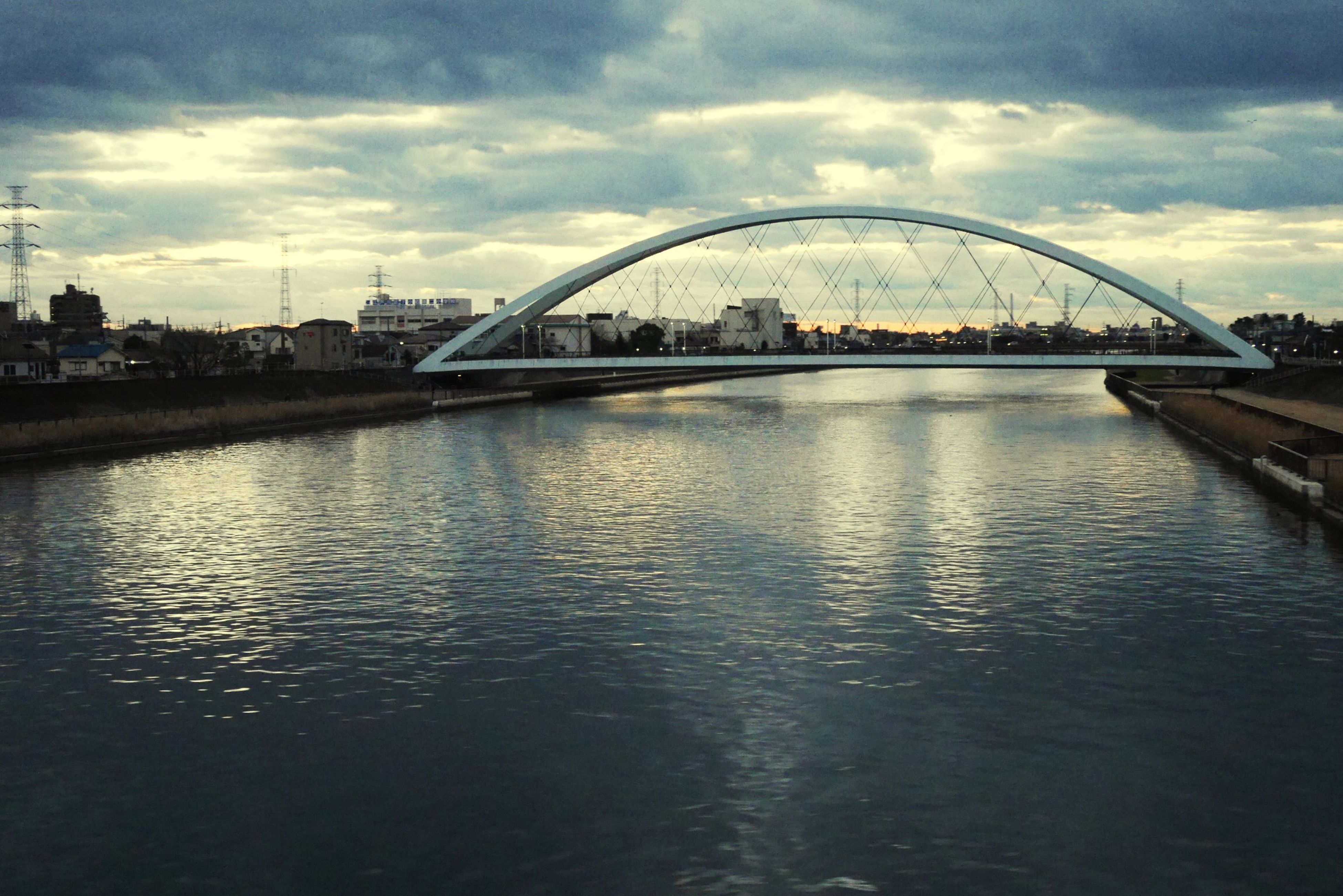 architecture, water, built structure, sky, river, bridge - man made structure, connection, waterfront, cloud - sky, building exterior, city, bridge, transportation, engineering, cloud, reflection, arch bridge, cloudy, rippled, arch