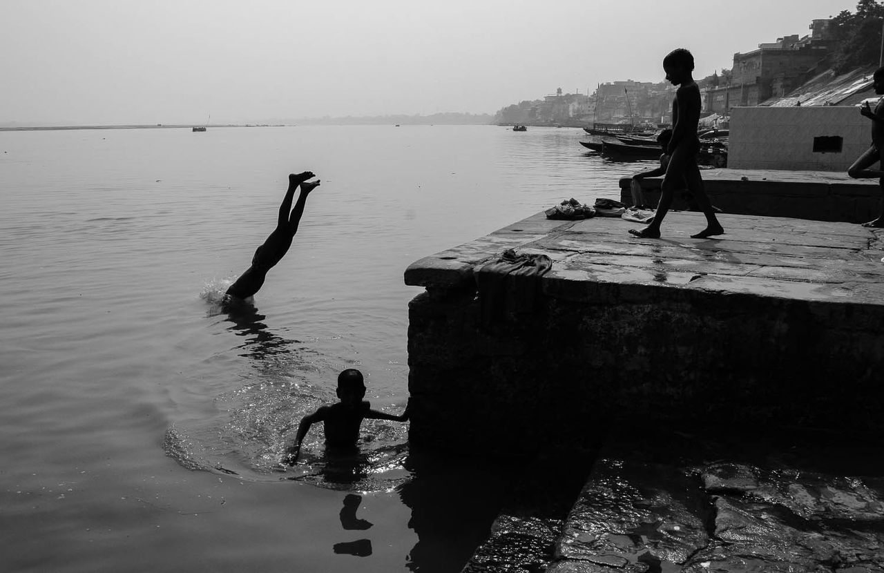 boys diving into the Ganges river in Varanasi, India Boys Childhood Day India Leisure Activity Lifestyles Men Nature Outdoors People Real People Sea Standing Varanasi, India Ganges, Indian Lifestyle And Culture, Bathing In The Ganges, Water