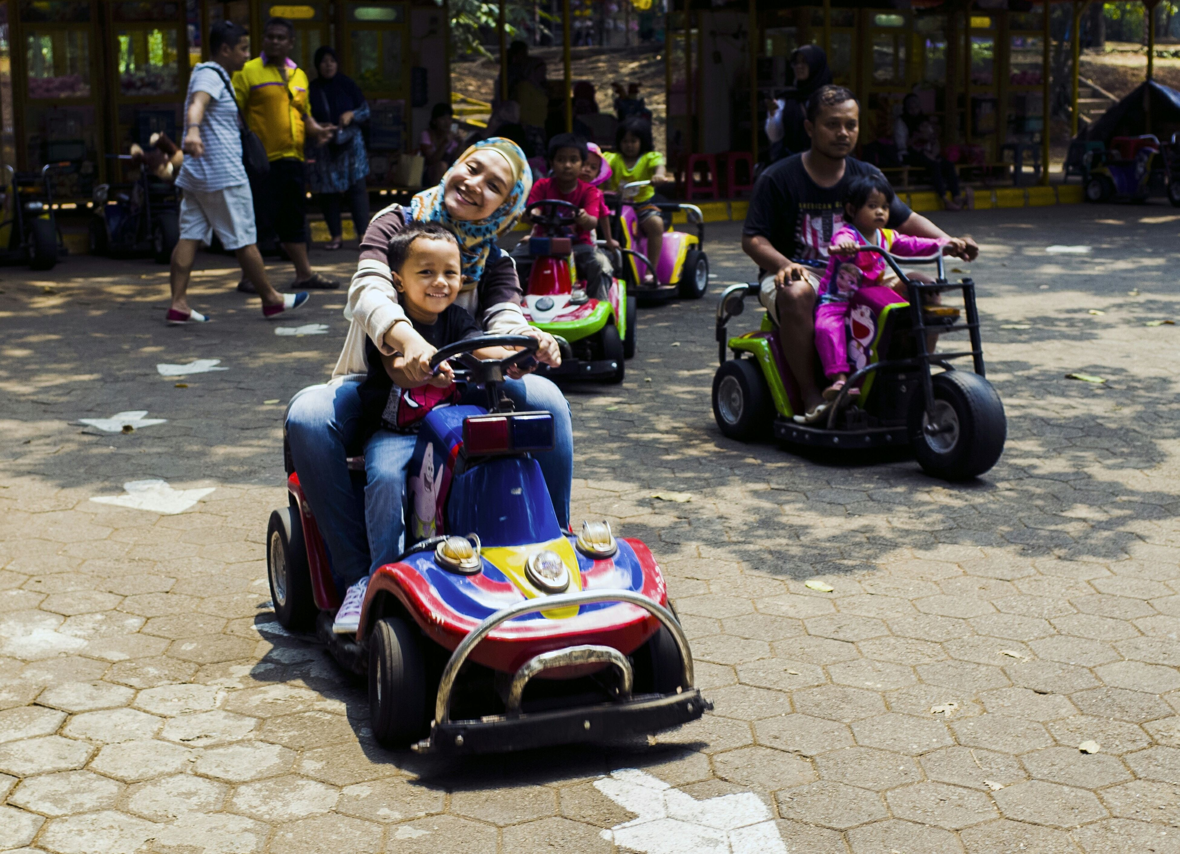 full length, lifestyles, leisure activity, casual clothing, land vehicle, street, person, transportation, childhood, mode of transport, boys, front view, togetherness, elementary age, girls, smiling, portrait
