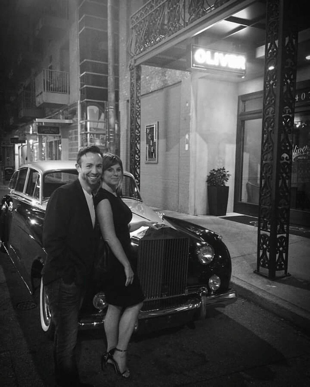 architecture, car, real people, lifestyles, built structure, one person, land vehicle, transportation, night, building exterior, full length, young adult, looking at camera, portrait, stationary, outdoors, young women, sitting, well-dressed, adult, people