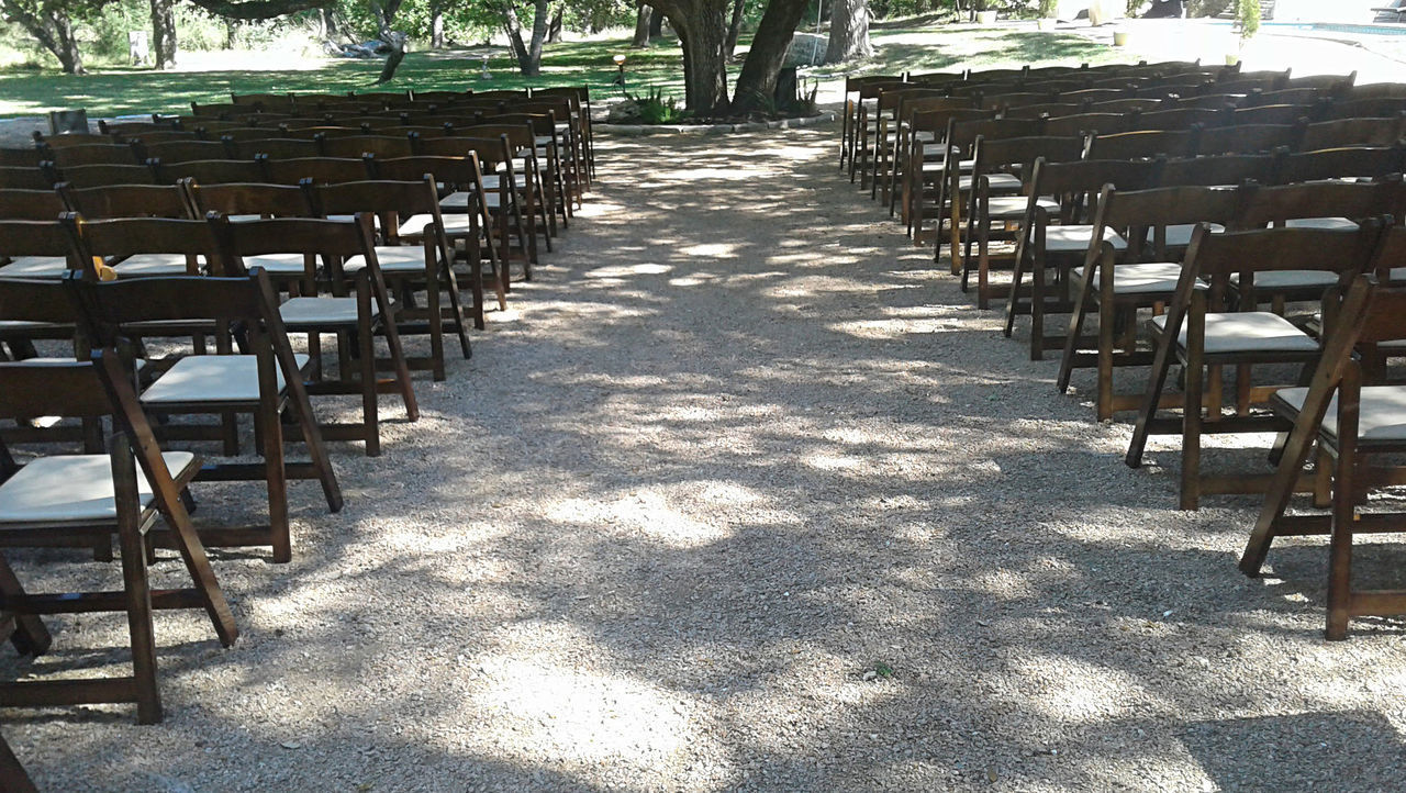 Wooden chairs are set up in rows outside in the shadow of trees, waiting for an event. Aisle Chair Day Empty Event In A Row Nature No People Outdoors Seat Seating Shadow Sunlight Tranquil Scene Tree Wedding