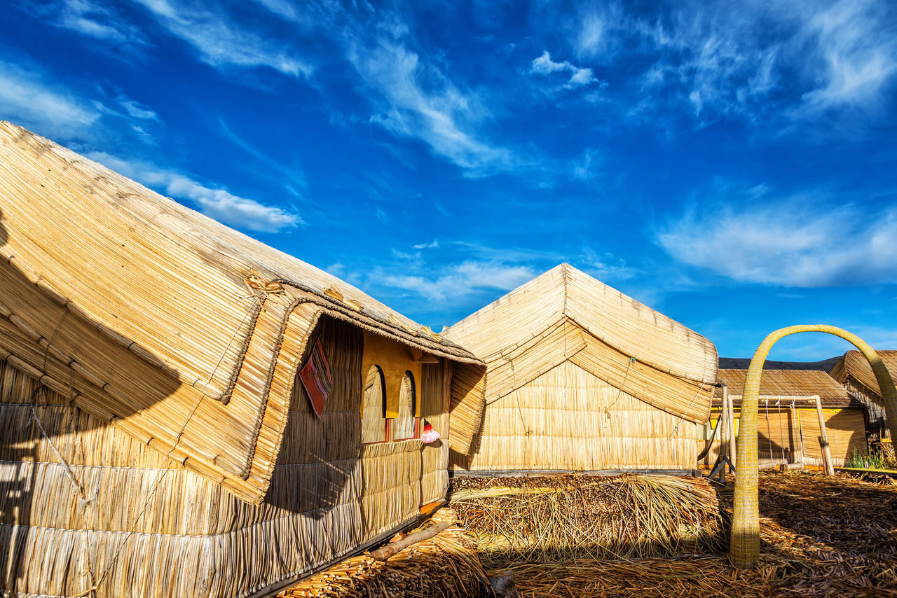 Small houses on Uros floating islands made out of reeds on Lake Titicaca near Puno, Peru America Andes Boat Destination Floating Inca Lake Landscape Latin Native Nature Peru Peruvian Puno Puno, Perú Reed Scenic Sky Titicaca Titicaca Lake Totora Travel Uros Uros Island Water