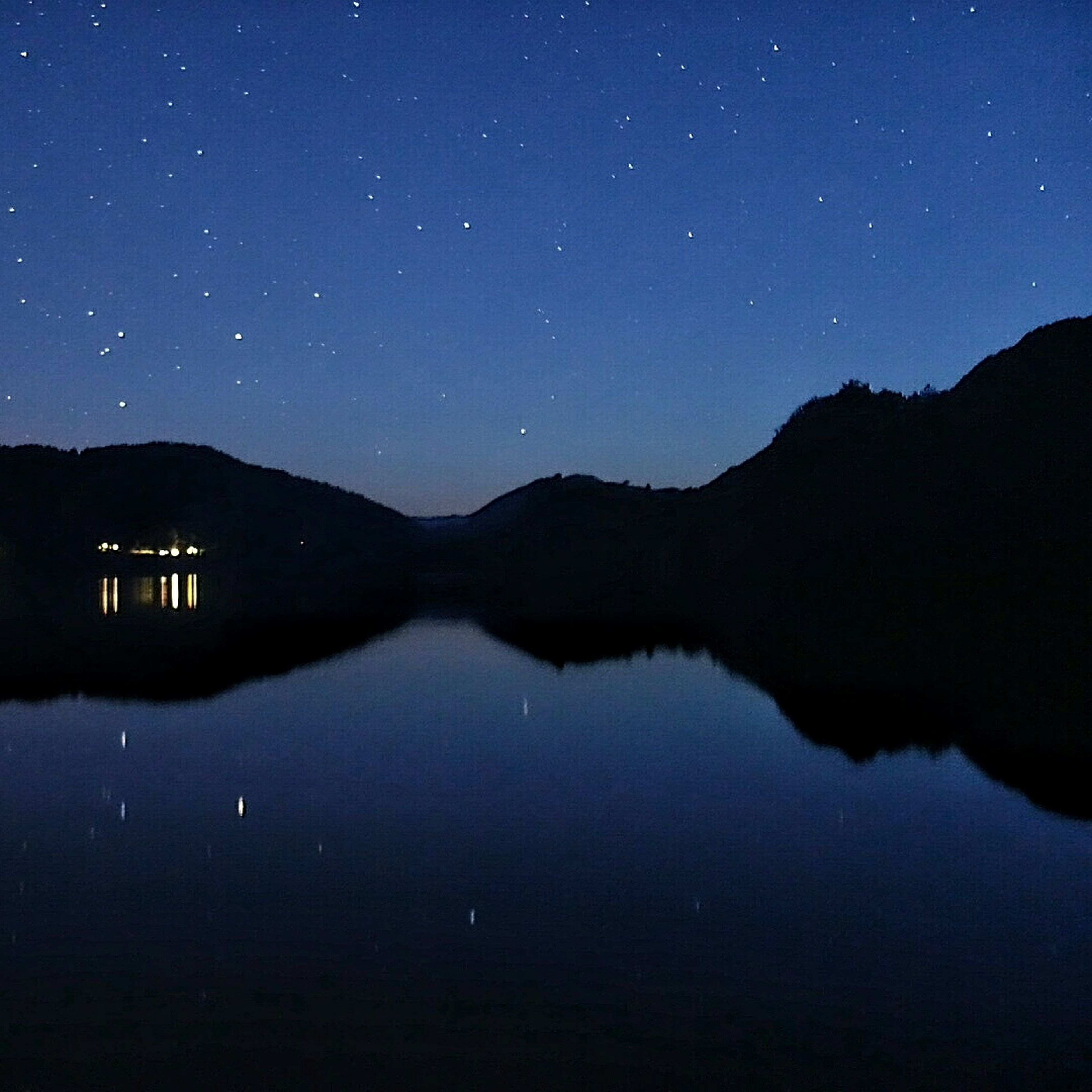 night, water, tranquil scene, scenics, tranquility, reflection, star - space, beauty in nature, sky, illuminated, mountain, star field, lake, astronomy, nature, waterfront, blue, idyllic, majestic, mountain range