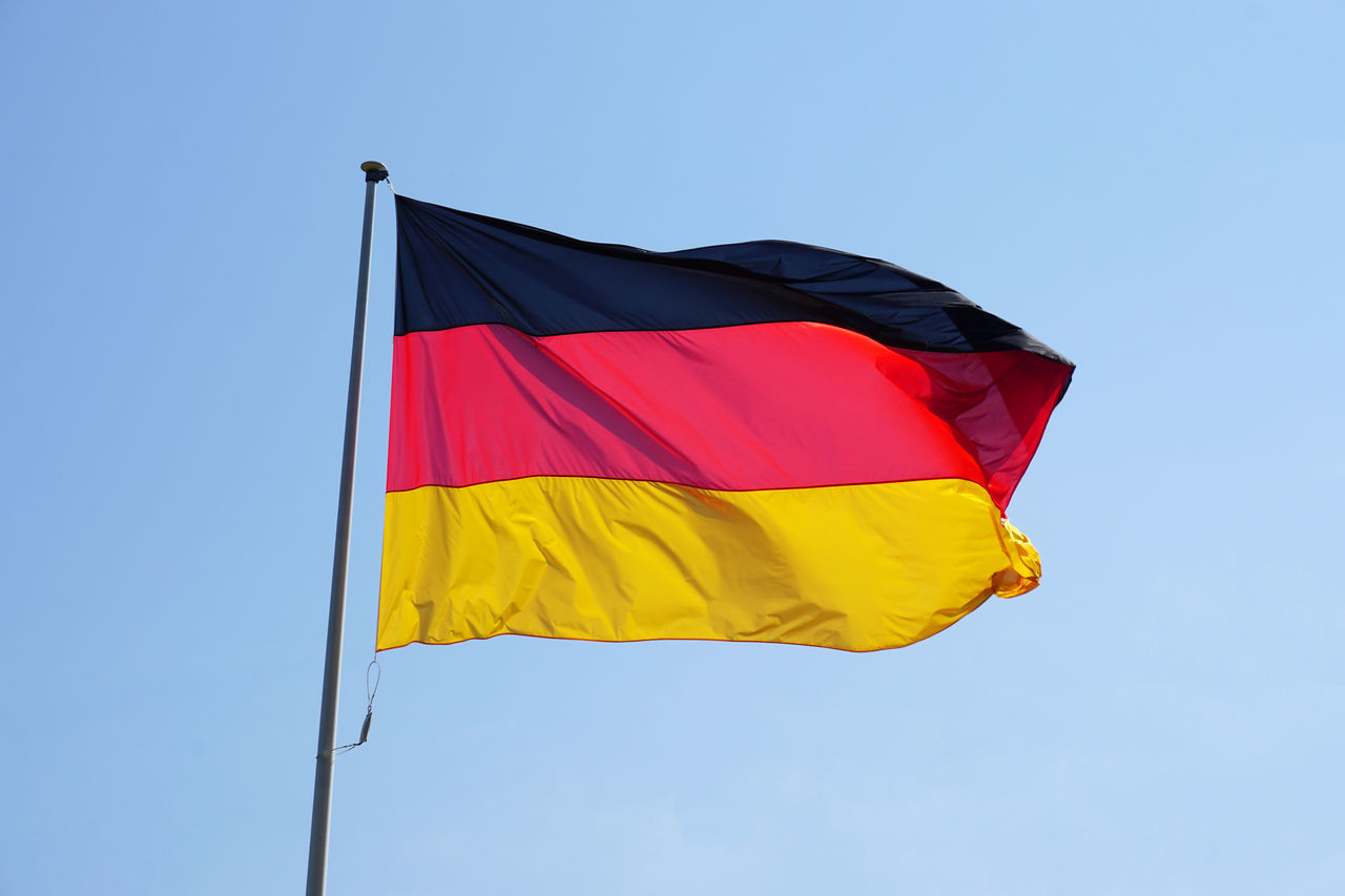 Low Angle View Of German Flag Against Clear Blue Sky