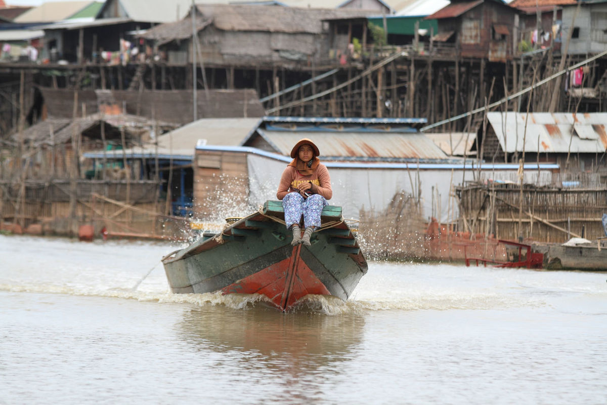 Boat Cambodia Day Focus On Foreground Motor Boat Outdoors River Rural Scene Seated Woman Sitting Stilt House Stilted Building Water Woman Wooden Buildings