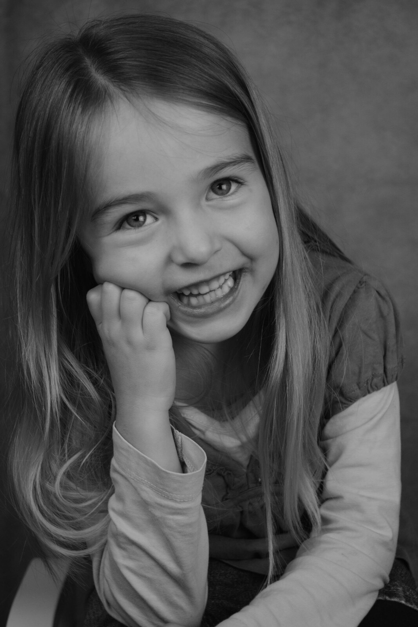 looking at camera, portrait, smiling, childhood, girls, one girl only, child, real people, one person, children only, happiness, headshot, close-up, cheerful, indoors, people, finger in mouth, human body part, day