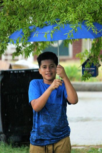 Boy Casual Clothing Child Enjoying Life Enjoyment Focus On Foreground Front View Happiness Innocence Innocent Leisure Activity Lifestyles Looking At Camera Person Playing In The Rain Portrait Rain Raining Smiling Standing Three Quarter Length The Portraitist - 2016 EyeEm Awards Young Adult Here Belongs To Me Color Palette The Street Photographer - 2017 EyeEm Awards