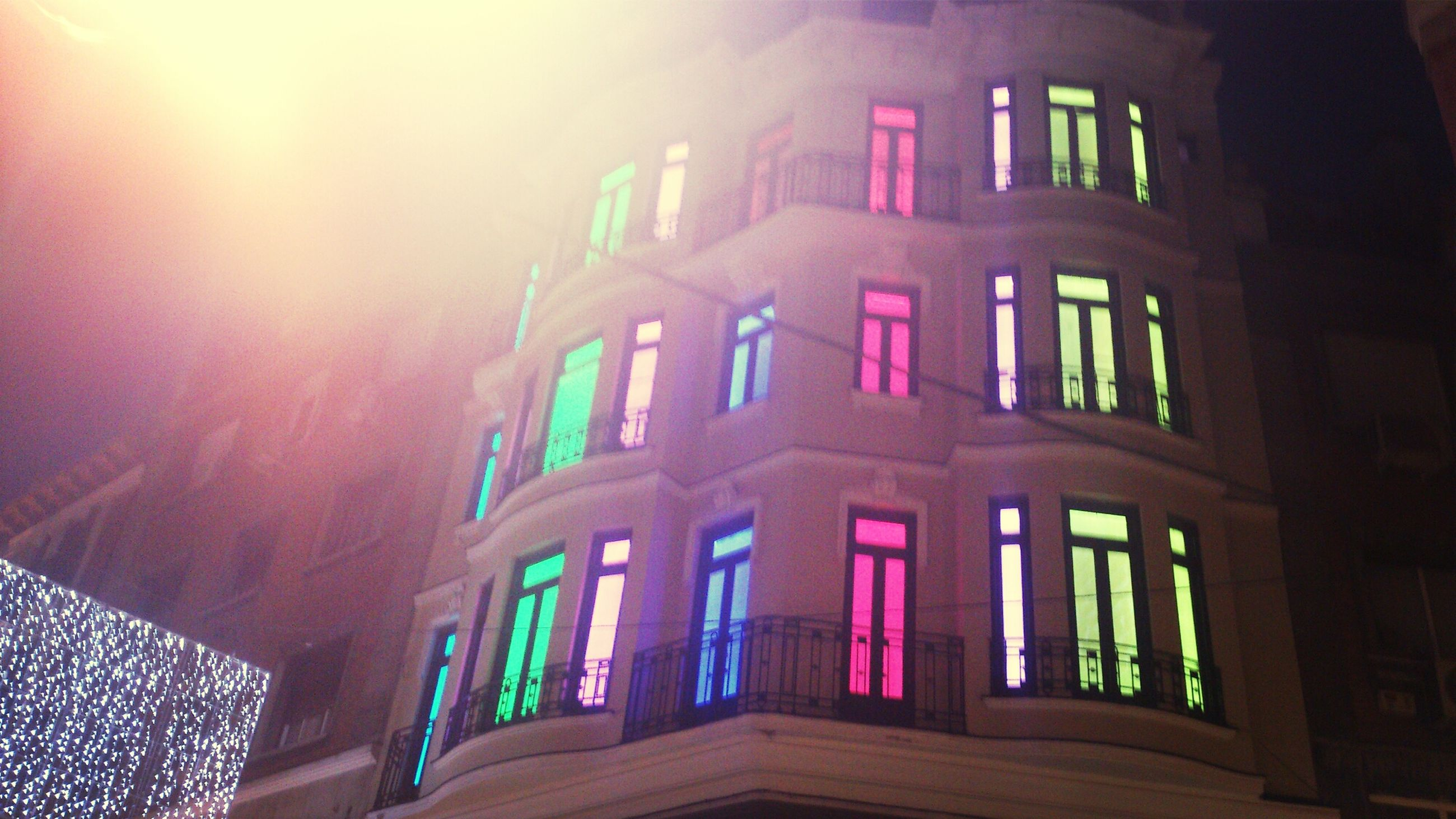 architecture, built structure, building exterior, low angle view, window, building, city, residential building, illuminated, sunlight, residential structure, no people, sky, night, outdoors, railing, arch, glass - material, facade