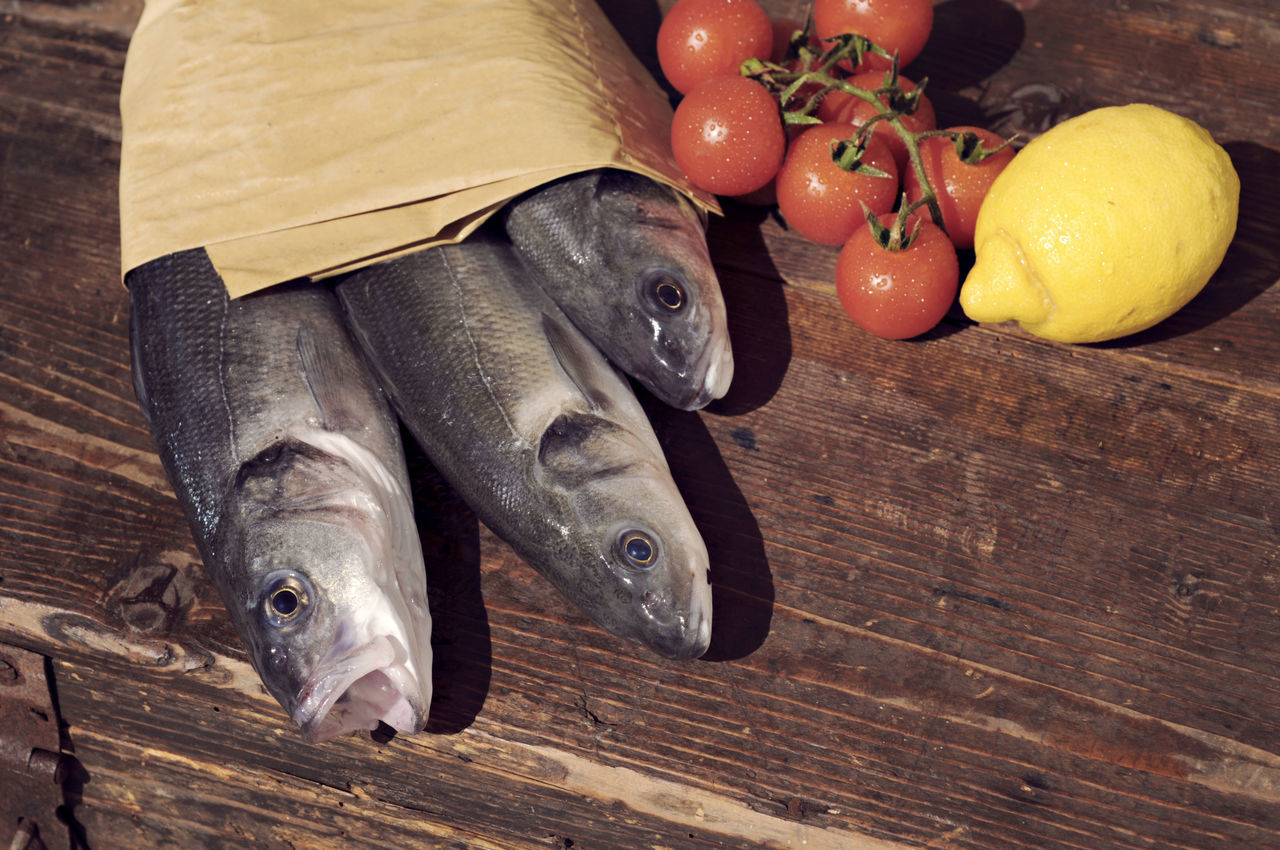 Sea bass fish Black Color Close-up Fish Ingredients Lemon No People Sea Bass Sea Food Still Life Table Tomato Wood - Material Wooden Market Reviewers' Top Picks Fresh On Market May 2016 Fresh On Market 2016