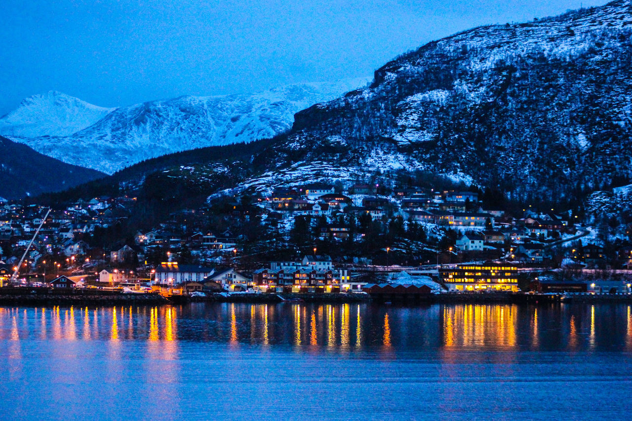 Scenic View Of Lake And Mountains During Winter At Dusk