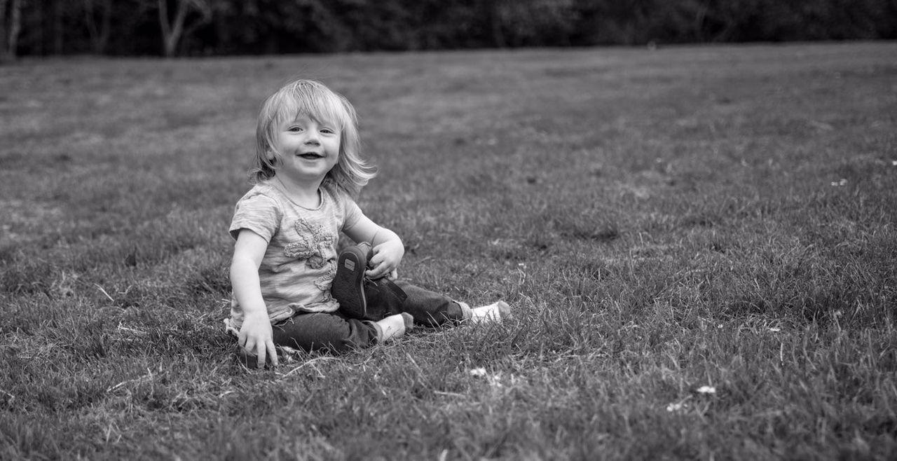 Happy Cute Girl Sitting On Grassy Field