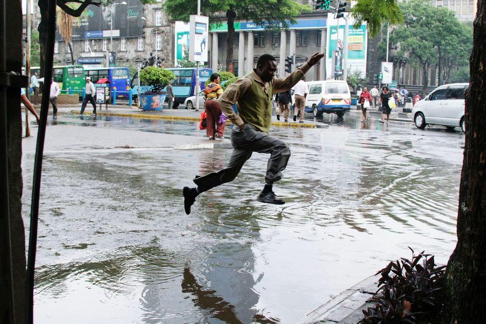 Man jumps a flooded a trench on a rainy afternoon in Nairobi. Rainy Days Raining RainyDay Man Jumps Jumping Man Floods Floods ❤ FloodsDeep