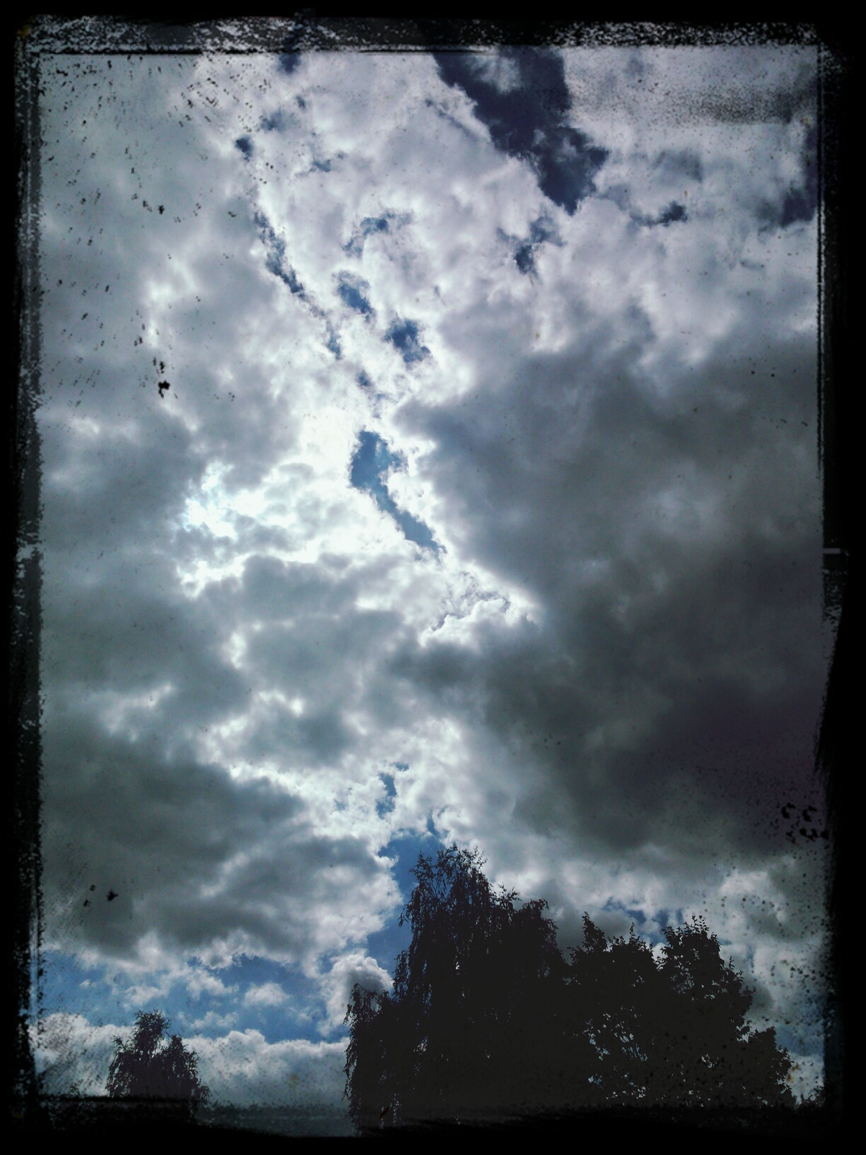transfer print, sky, cloud - sky, auto post production filter, cloudy, low angle view, weather, cloud, tree, tranquility, overcast, beauty in nature, scenics, tranquil scene, silhouette, nature, storm cloud, cloudscape, outdoors, dramatic sky