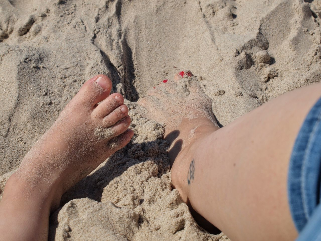 Beach Sand Real People Human Body Part Human Leg Legs Child Two People Two Legs Legs In Sand Red Nails Red Nail Polish Tattoo Leg Tattoo Togetherness Sunlight Vacations Outdoors Leisure Activity Day Close-up Women Low Section Adult People