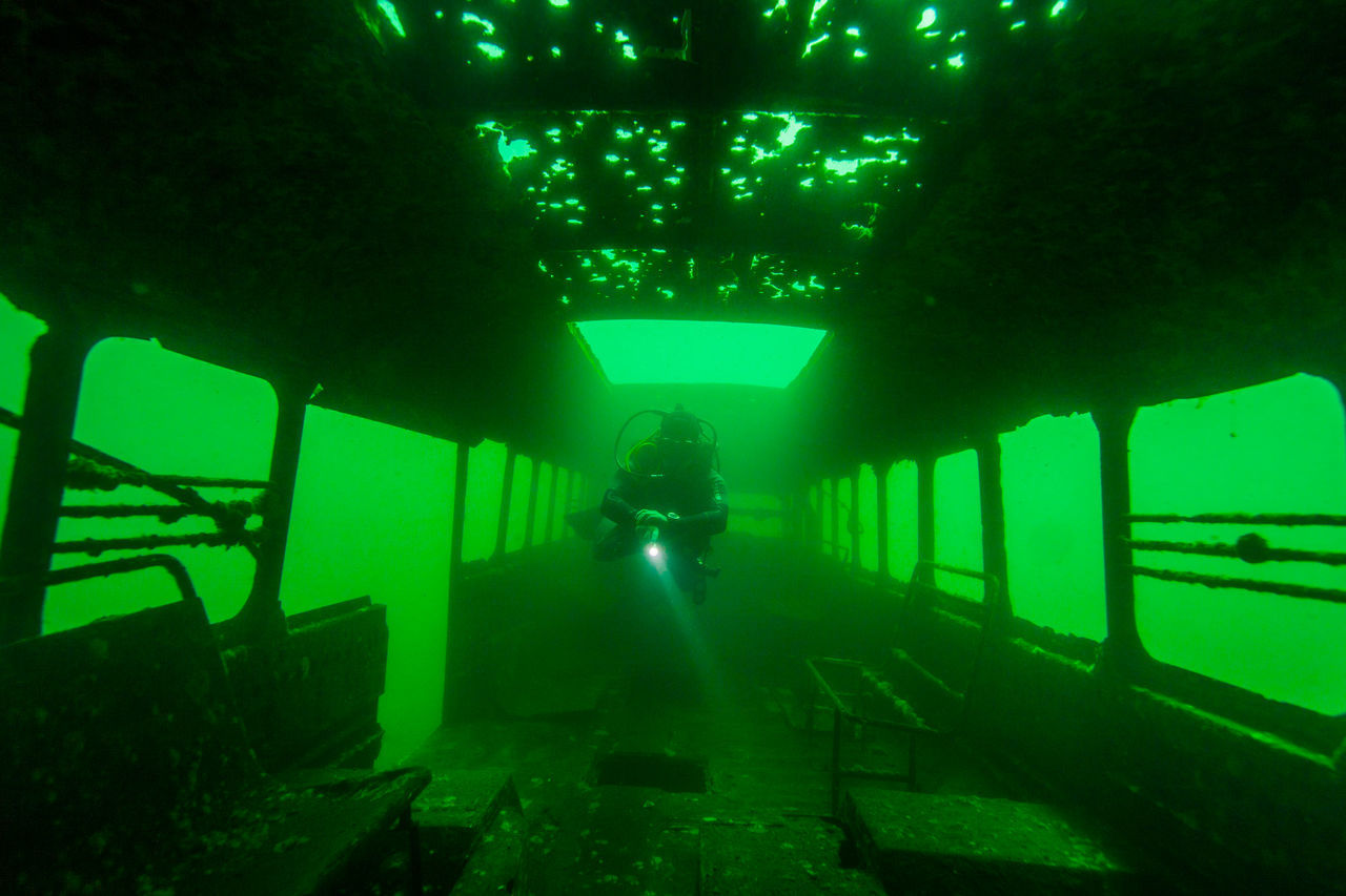 A diver explores a purposefully sunken bus at Bass Lake, a popular dive site located south of Johannesburg, in South Africa. Shot on a Canon 5D Mk II using a 17-40mm f4 lens in an Ikelite housing. Adventure Diver Diving Equipment Divingphotography Exploration Floating Freedom Green Green Color Green Color Leisure Activity Light Neutral Buoyancy SCUBA Scuba Diver Scuba Diving Silhouette Torchlight Underwater Wreck Wreck Diving