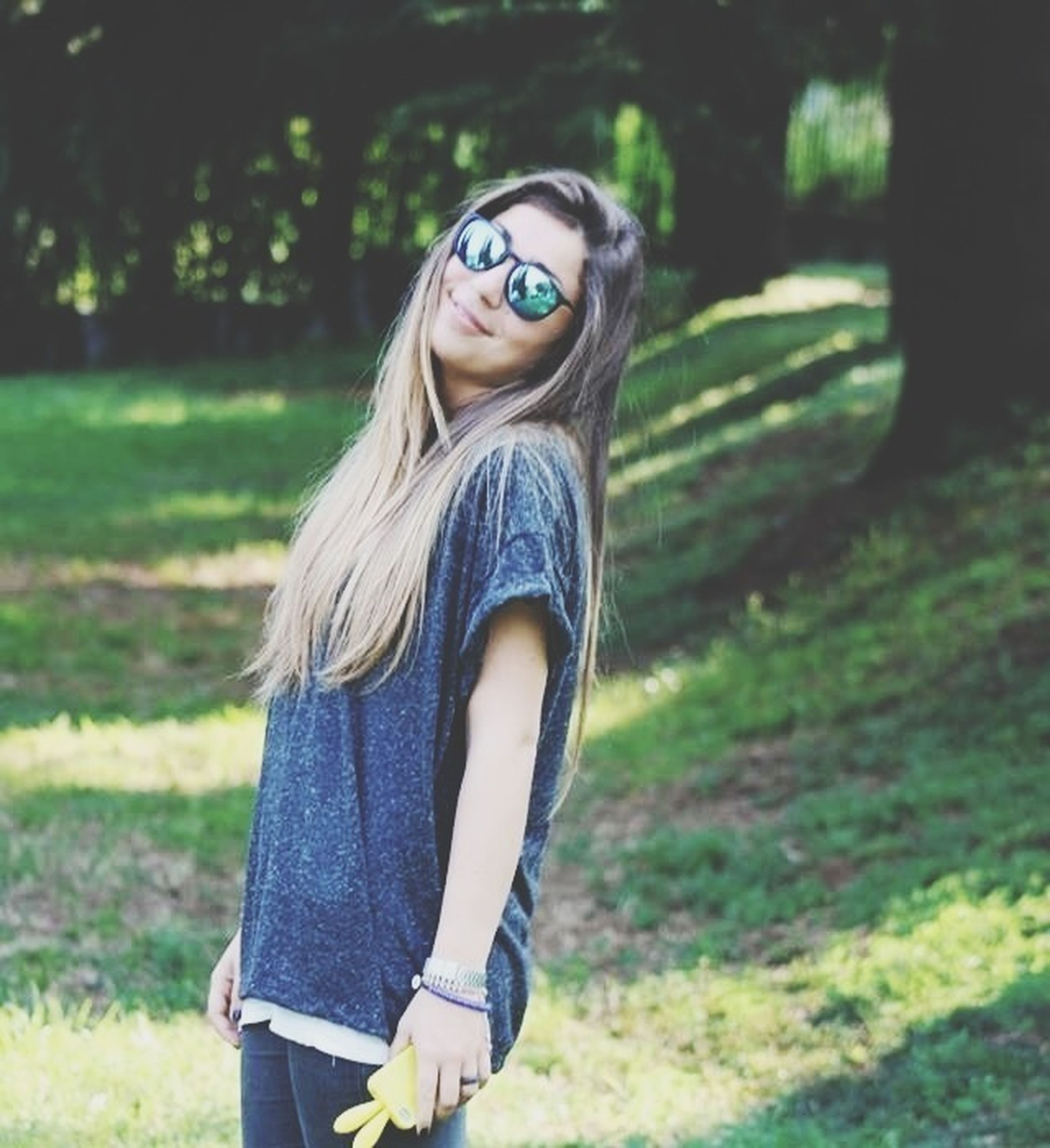 young adult, lifestyles, young women, focus on foreground, casual clothing, person, grass, leisure activity, portrait, looking at camera, long hair, front view, standing, sunglasses, field, smiling, park - man made space