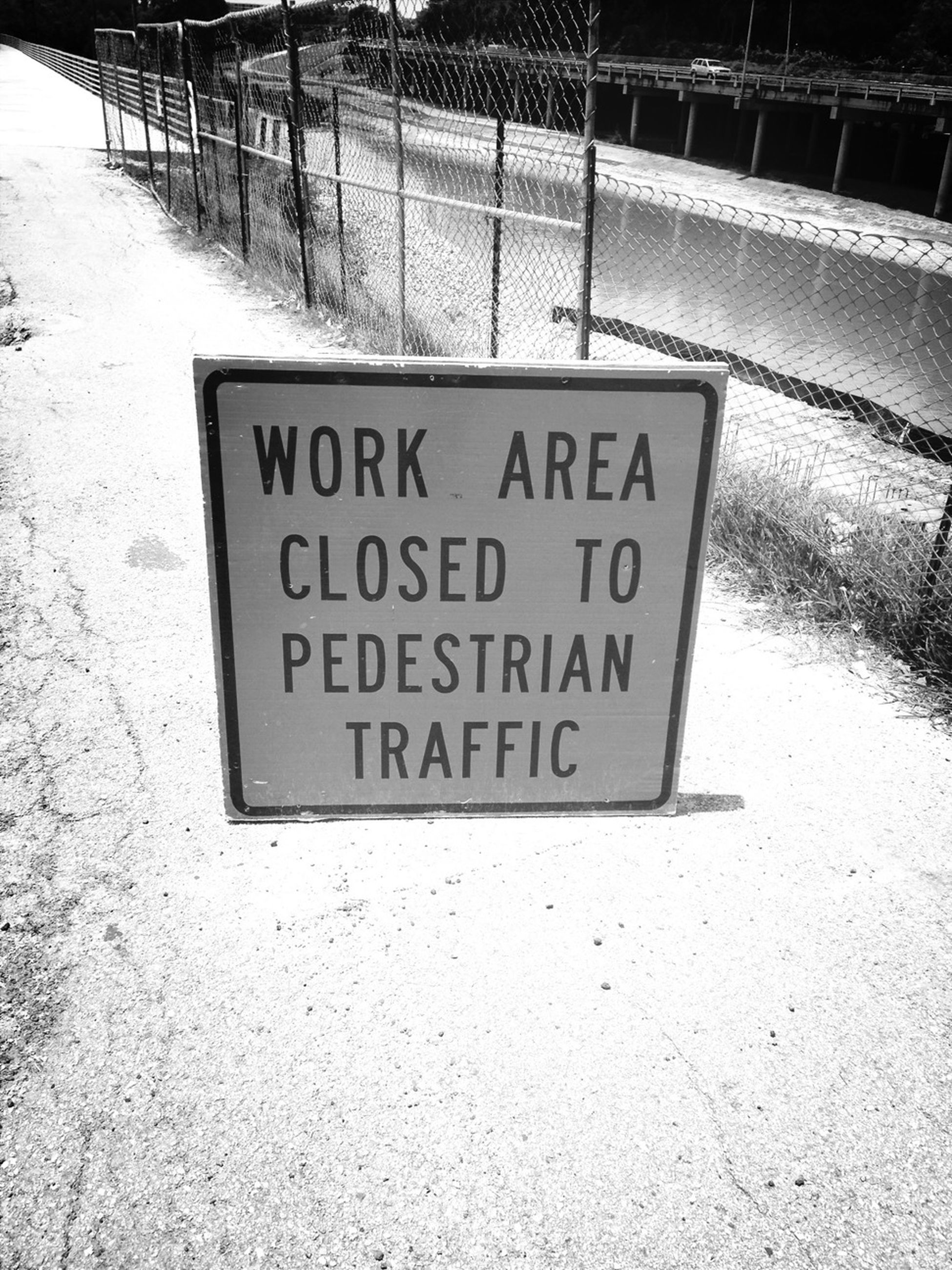 text, western script, communication, information sign, sign, capital letter, information, warning sign, non-western script, guidance, outdoors, road sign, day, no people, arrow symbol, wall - building feature, safety, directional sign, built structure, signboard