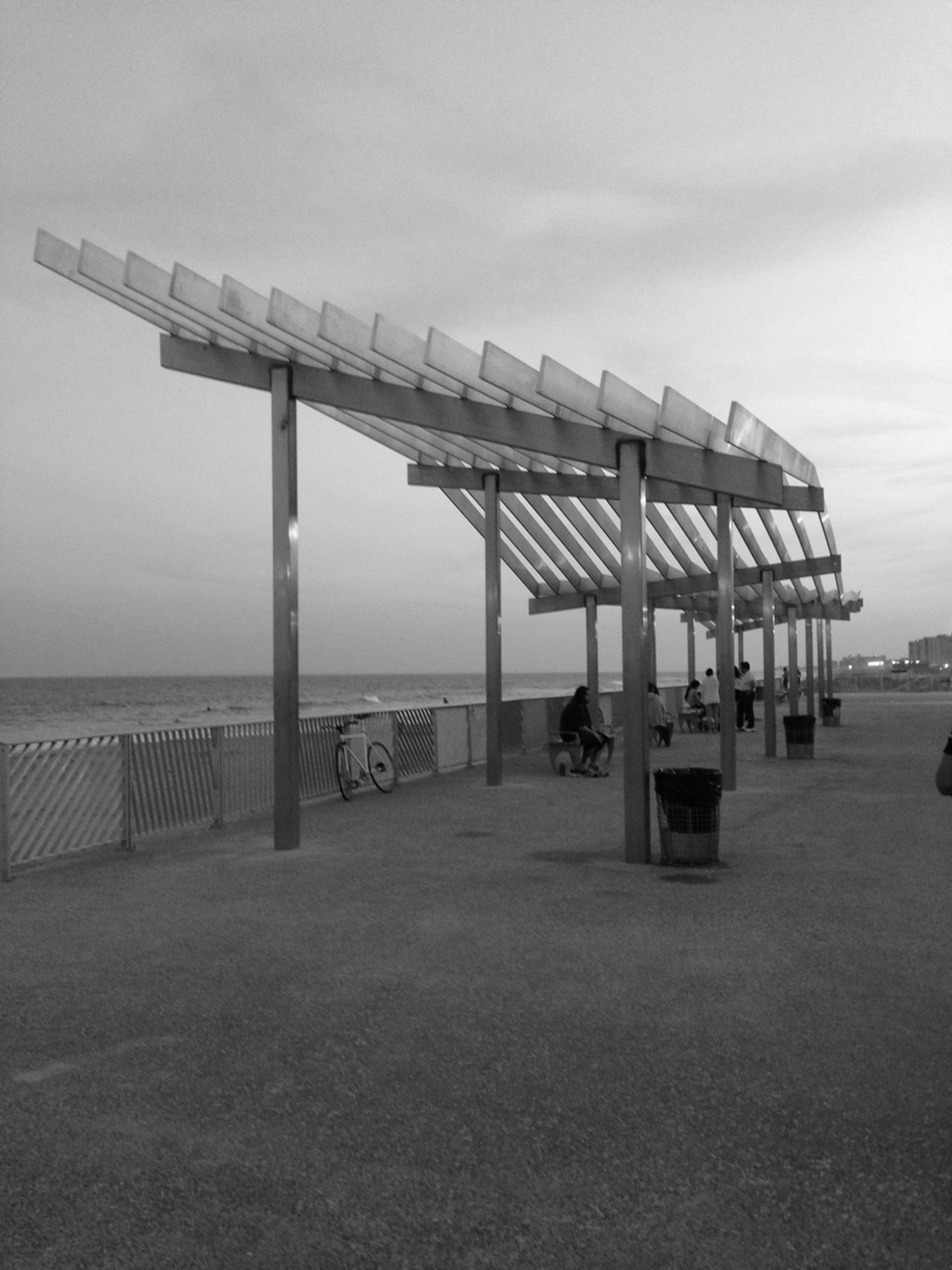 sea, beach, built structure, water, architecture, horizon over water, sky, sand, shore, pier, incidental people, tranquility, tranquil scene, day, nature, building exterior, outdoors, cloud - sky, railing, scenics