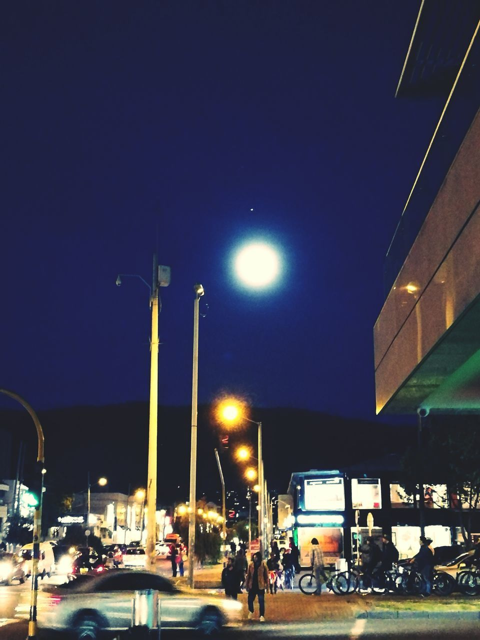 night, illuminated, transportation, street light, mode of transport, car, land vehicle, built structure, outdoors, sky, building exterior, architecture, moon, road, clear sky, city, no people