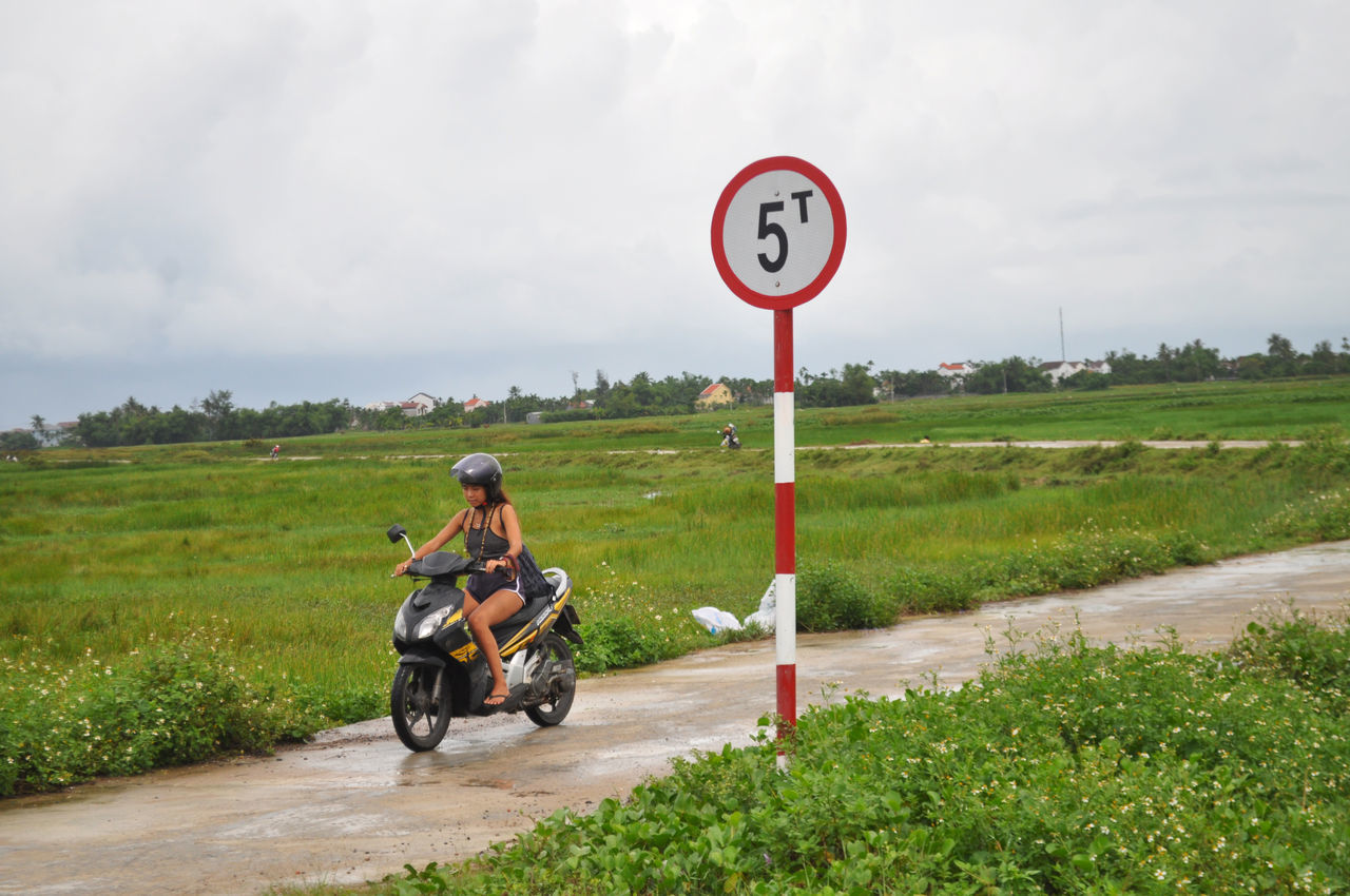 Girl on motorcycle on lane through fields near Hoi An, Vietnam. Editorial  Farms Fields Girls Hoi An Landscape Lanes Motorbikes Motorscooters Outdoors Riding Rural Scene Sky Traffic Signs Transport Vietnam