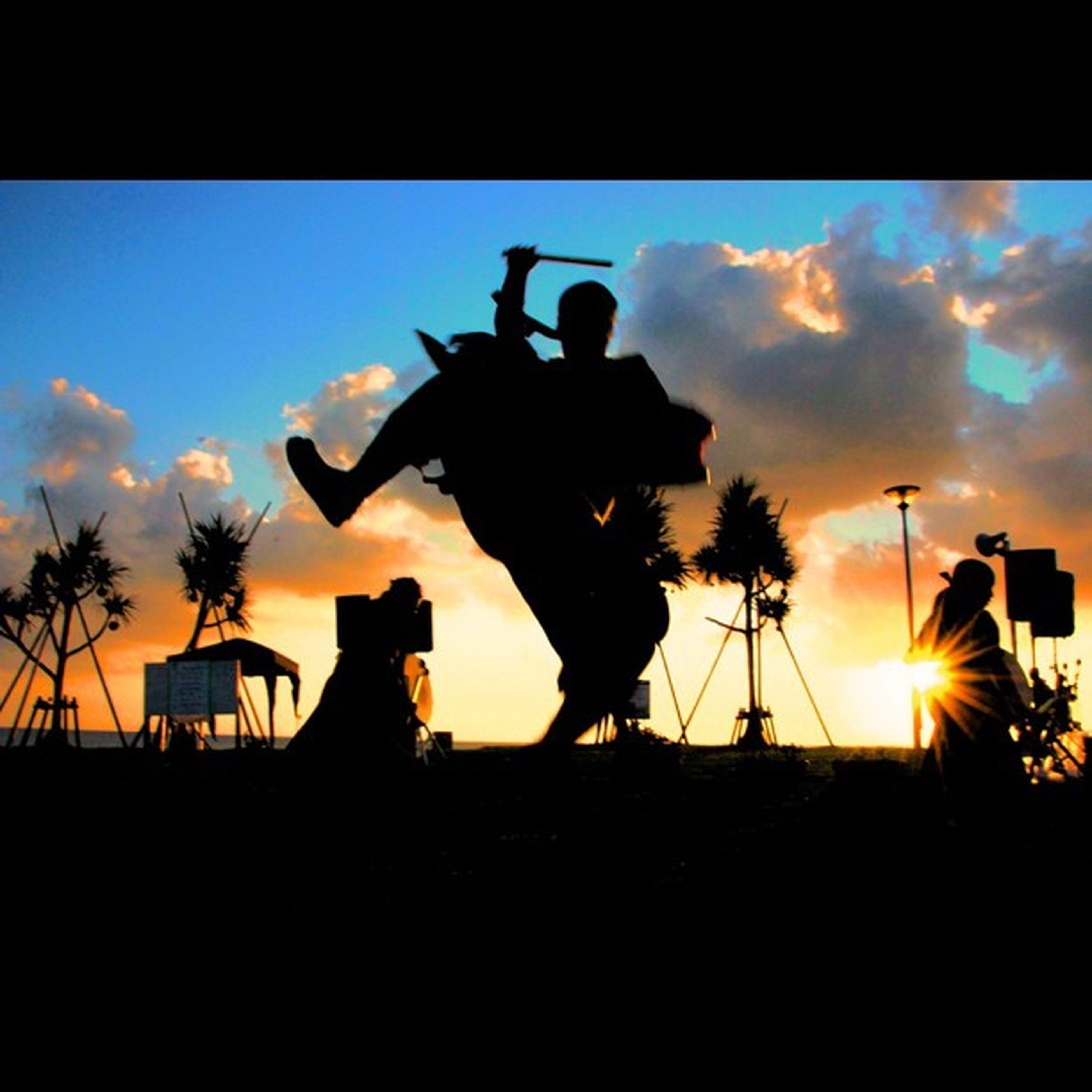sunset, silhouette, sky, cloud - sky, sun, cloud, palm tree, sunlight, transfer print, sculpture, auto post production filter, orange color, sunbeam, nature, art and craft, horse, tree, outdoors, low angle view, men