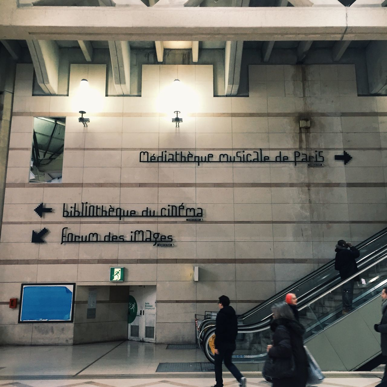text, western script, communication, real people, walking, built structure, steps and staircases, indoors, illuminated, architecture, men, guidance, subway station, women, day, people