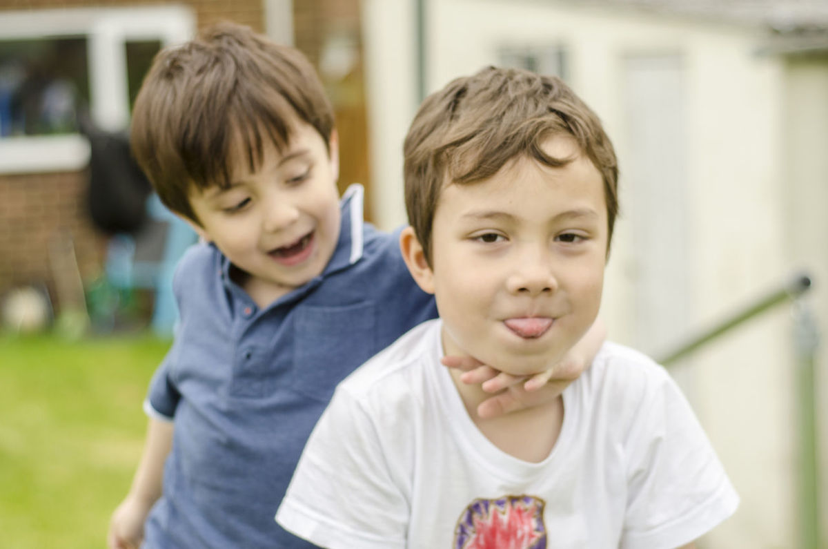 Two young brothers having fun, posing for the camera int he back garden. Back Garden Boy Boys Brothers Cheeky Child Childhood Children Cute Elementary Age Family Fun Garden Happy Innocence Outside Picnic Table Portrait Posing Sticking Out Tongue Young
