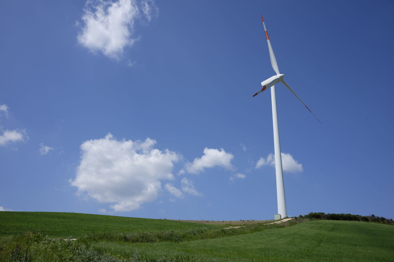 Windmill On Grassy Field Against Sky