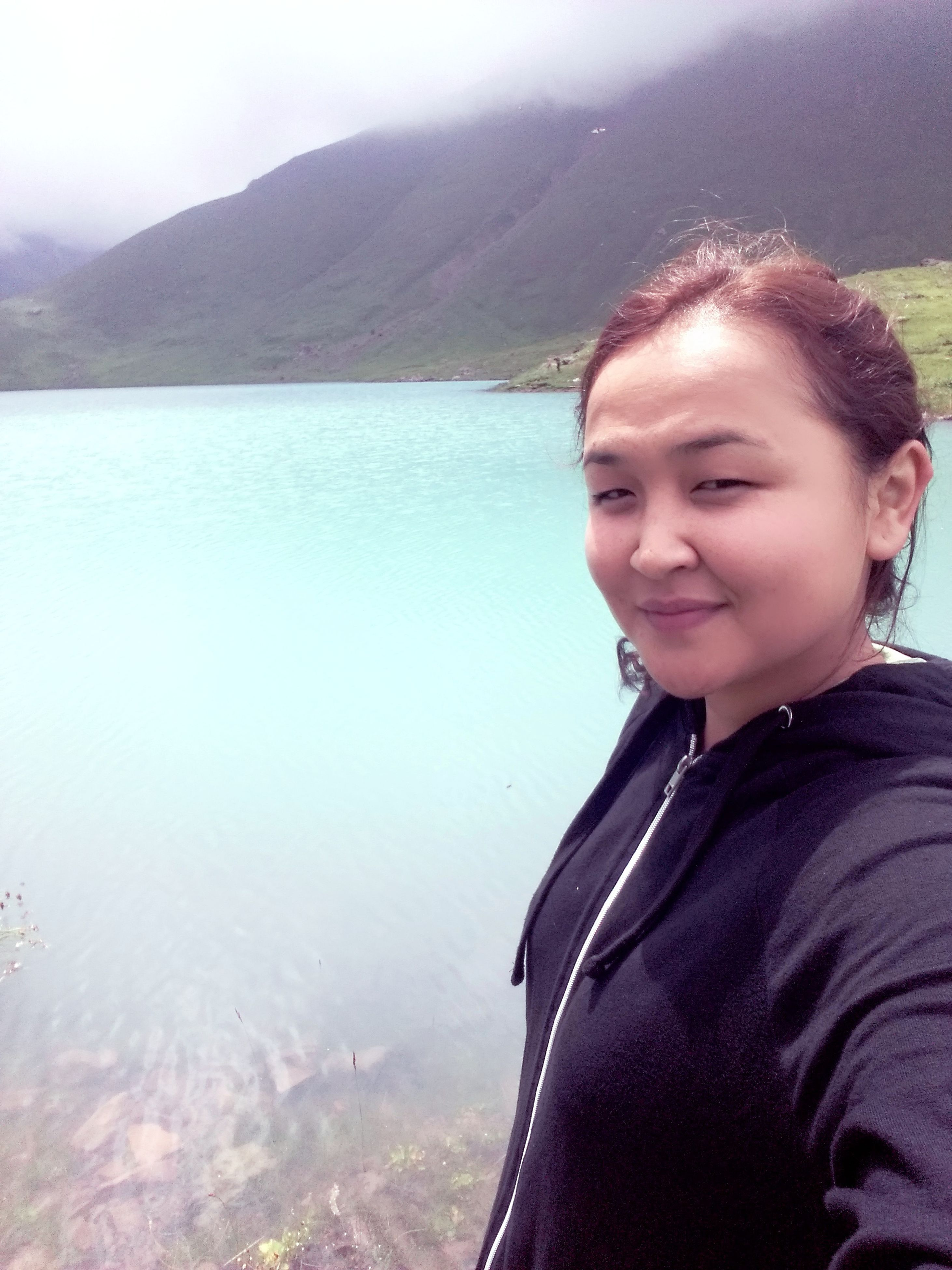 water, mountain, smiling, portrait, warm clothing, looking at camera, leisure activity, lifestyles, jacket, scenics, person, tranquil scene, blue, mountain range, tranquility, nature, beauty in nature, day, young adult, vacations, non-urban scene