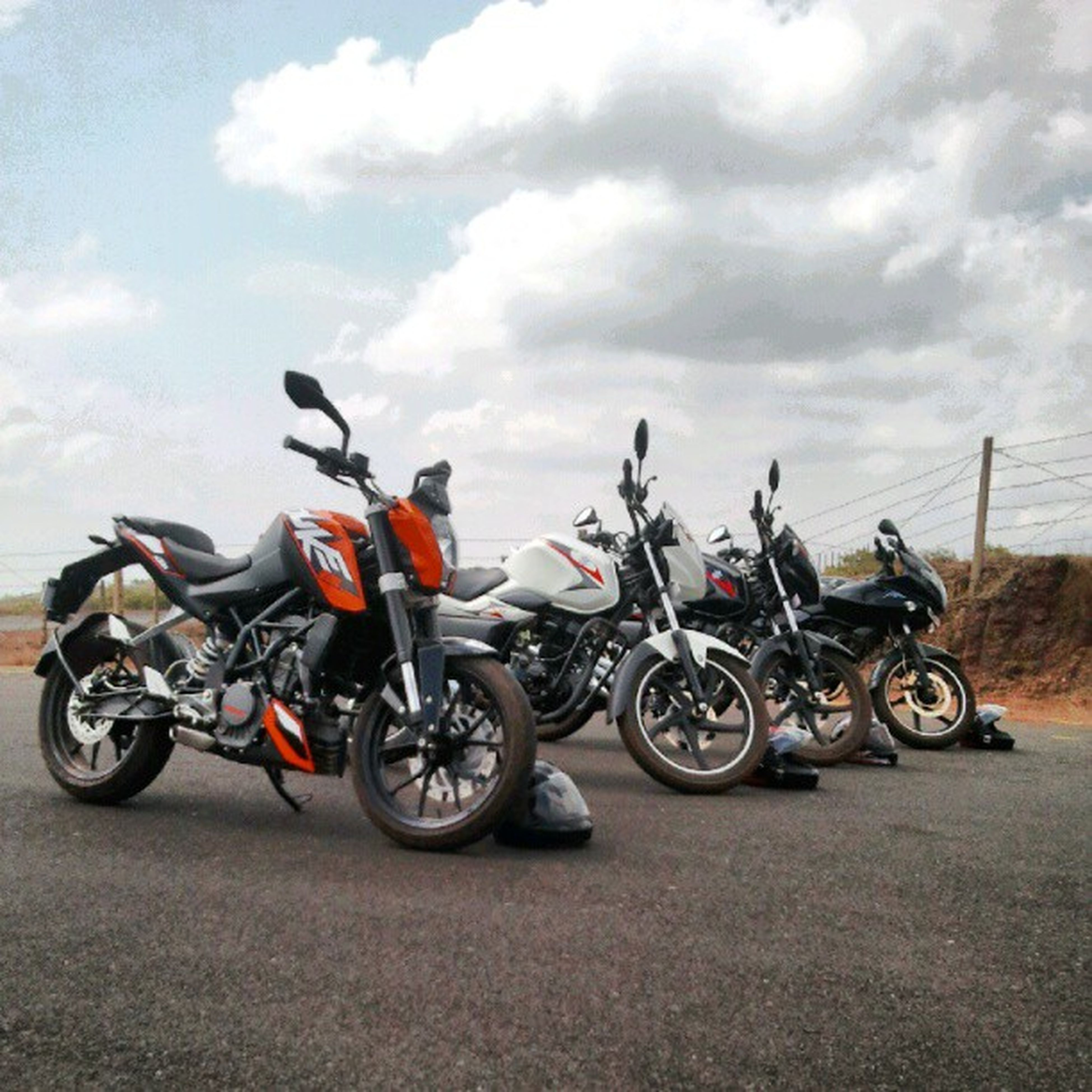 bicycle, transportation, land vehicle, mode of transport, stationary, parked, parking, sky, motorcycle, cloud - sky, travel, day, side view, riding, outdoors, street, car, no people, road, parking lot