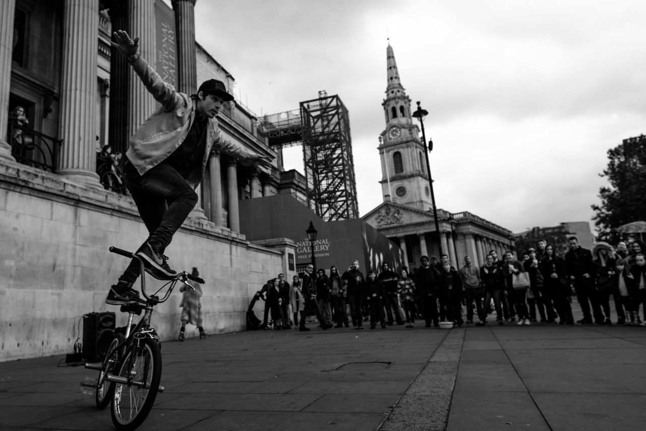 architecture, building exterior, built structure, real people, men, bicycle, city, street, transportation, outdoors, sky, large group of people, women, day, protestor, adult, people
