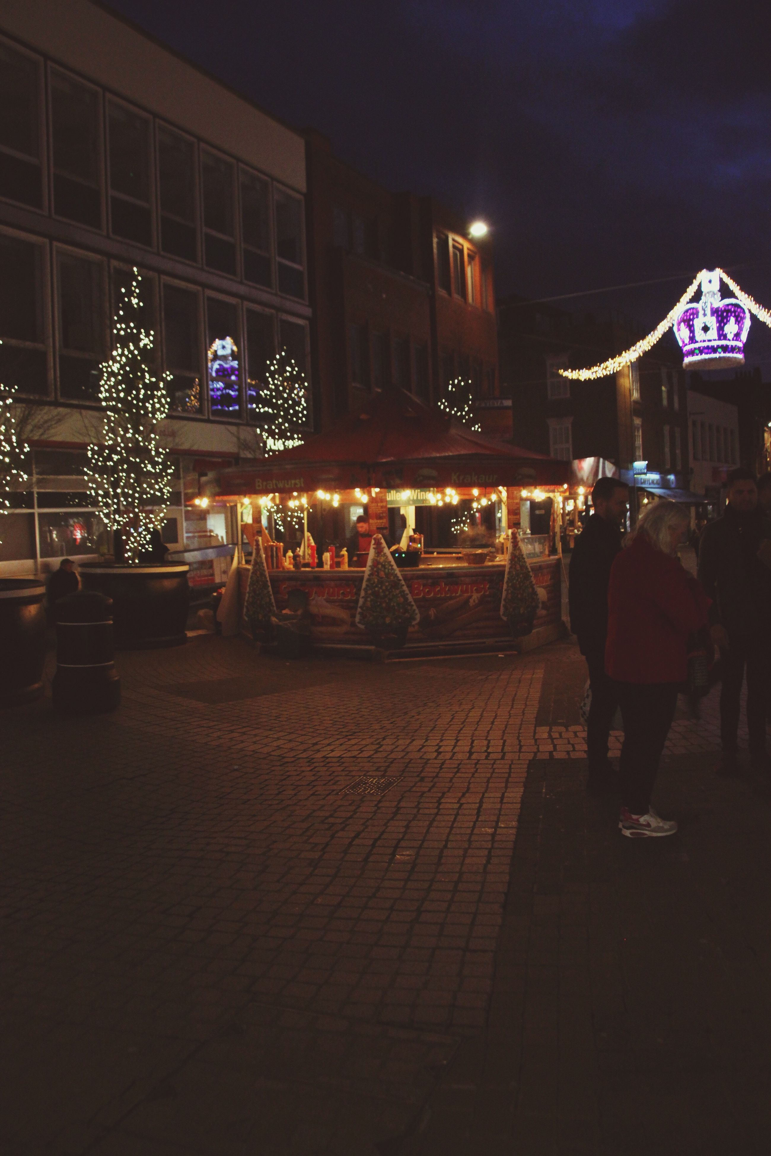 night, illuminated, nightlife, christmas lights, bar - drink establishment, built structure, city, christmas, travel destinations, christmas decoration, architecture, people, men, adult, outdoors, adults only, pub, sky