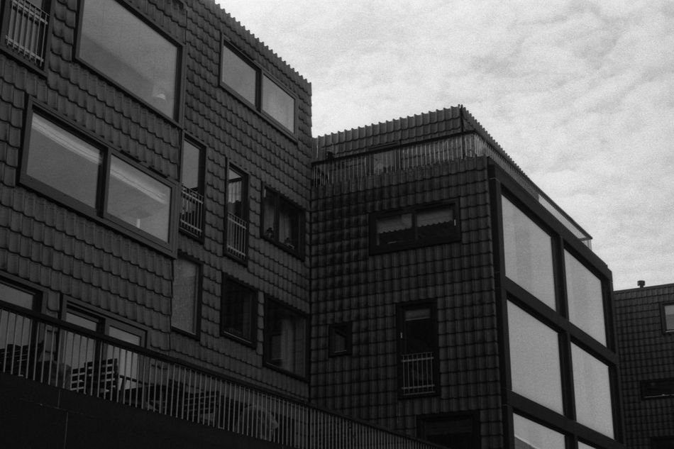 Apartments in the City 35mm Film Analogue Photography Apartment Architecture Black & White Building City Clouds Contrast Fomapan100 Glass Modern Modern Architecture Rodinal Sky Urban Window