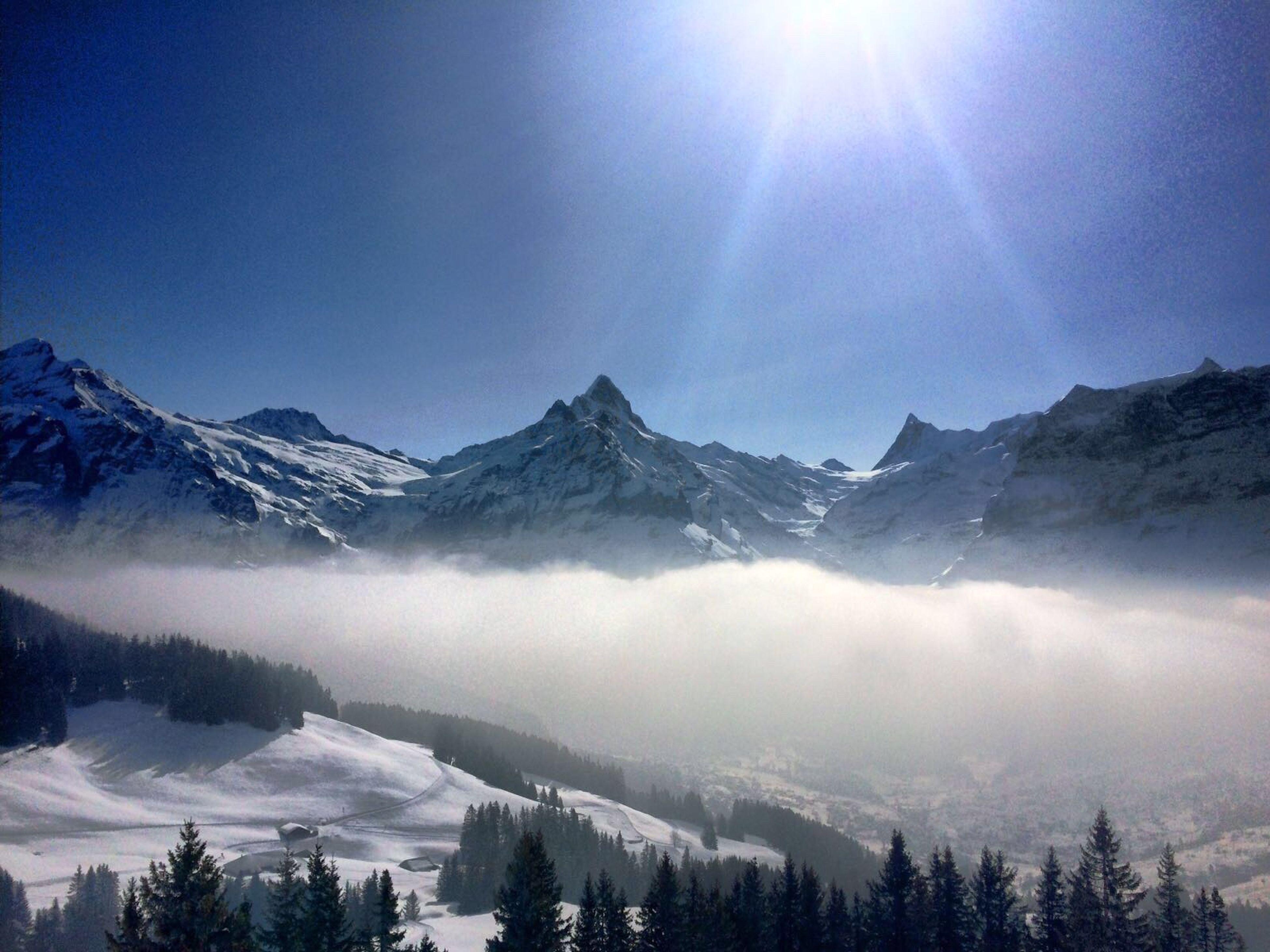 snow, mountain, winter, cold temperature, mountain range, tranquil scene, beauty in nature, scenics, tranquility, snowcapped mountain, season, weather, nature, tree, landscape, sun, sunlight, blue, sunbeam, covering