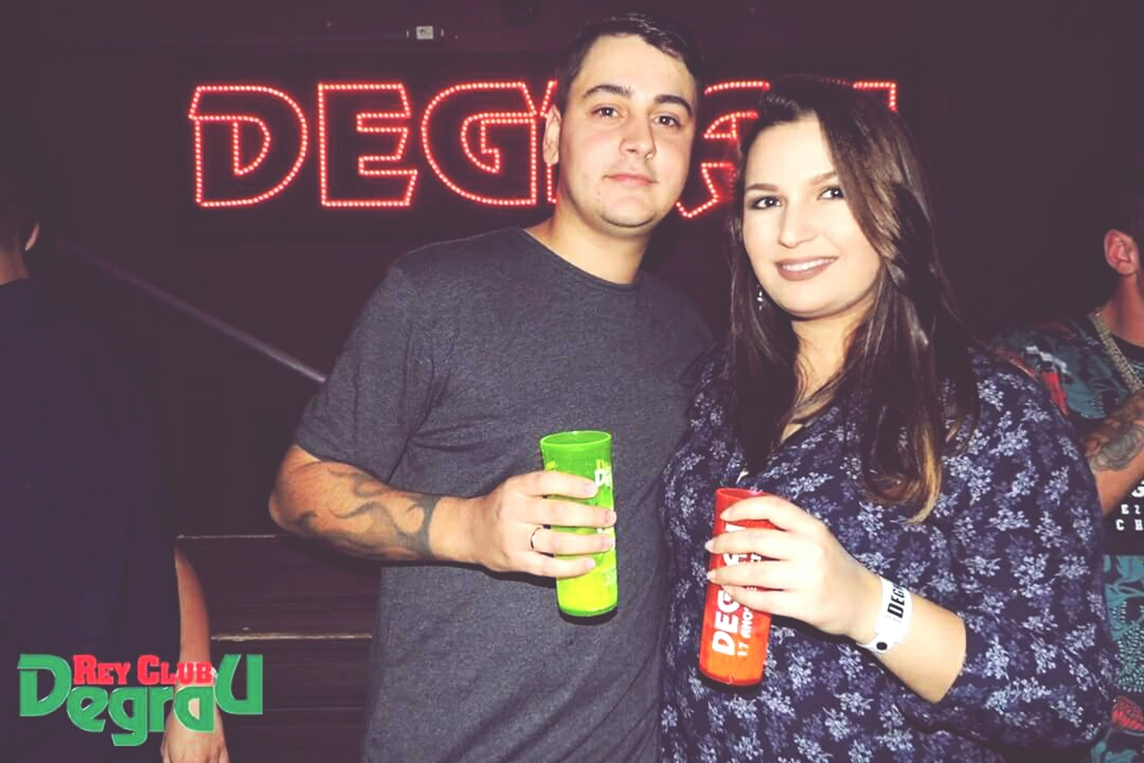 two people, looking at camera, front view, text, drink, portrait, togetherness, communication, young adult, food and drink, young women, young men, casual clothing, real people, lifestyles, night, love, refreshment, leisure activity, drinking, holding, bonding, smiling, happiness, indoors, illuminated, friendship