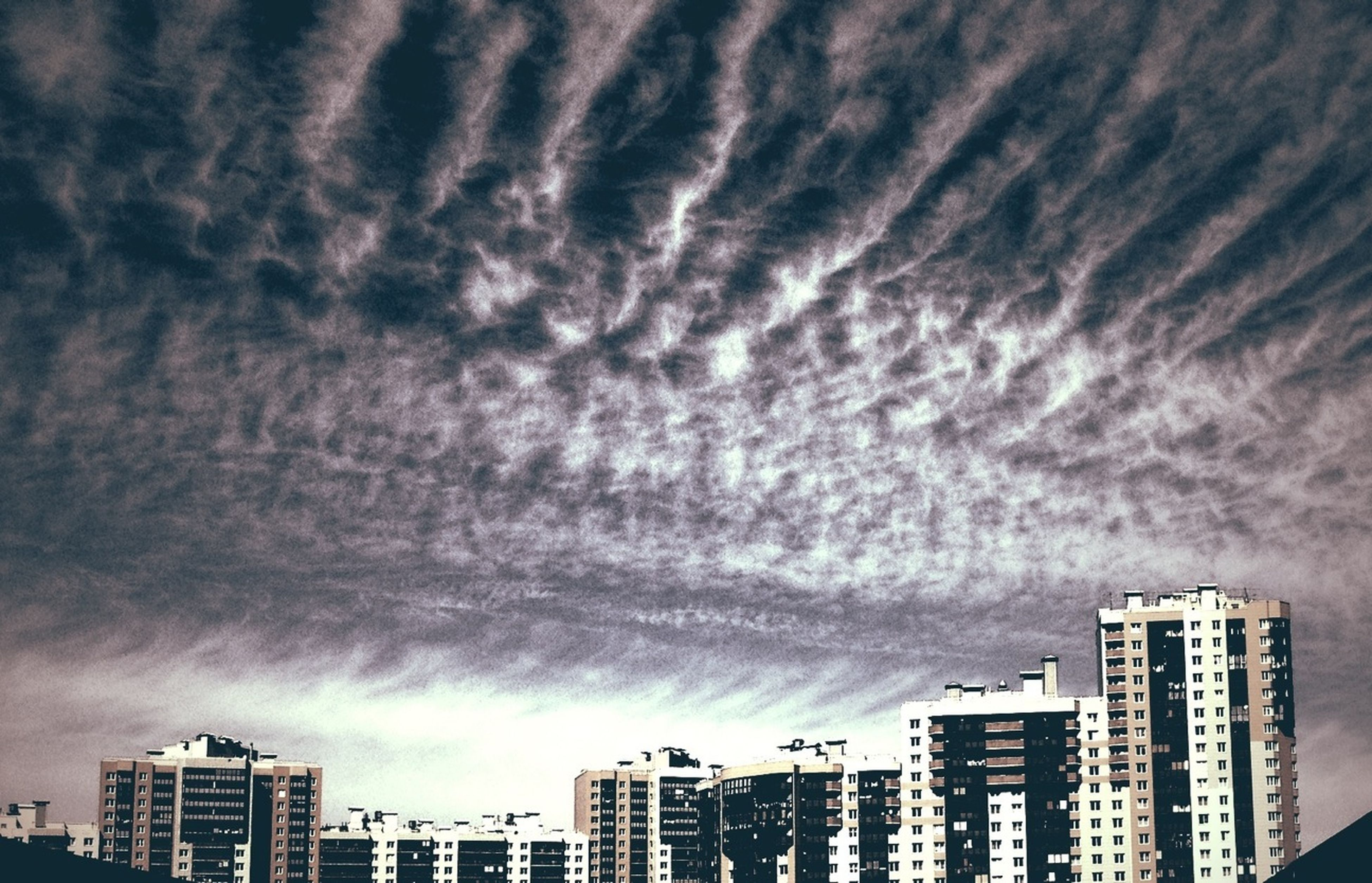 building exterior, architecture, built structure, sky, city, cloud - sky, cloudy, weather, low angle view, overcast, building, residential building, skyscraper, storm cloud, cloud, cityscape, residential structure, modern, outdoors, no people