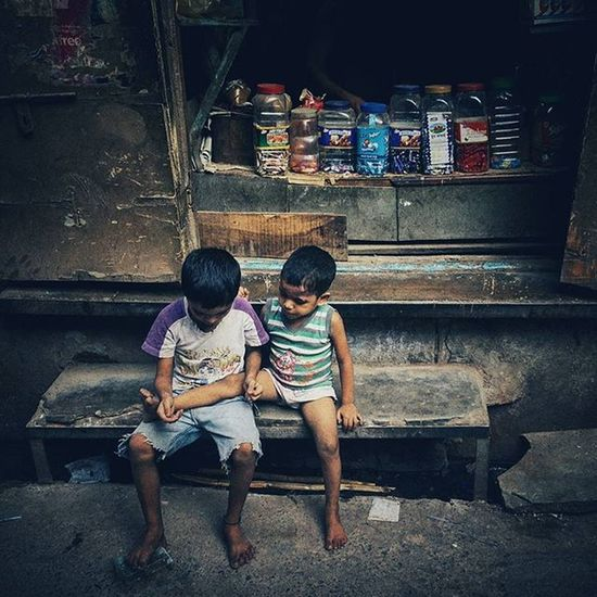 """Two Indian kids play 'Doctor Patient' as they sit outside a shop in the old quarters of Delhi, India. When I asked them what they were doing, the one on the left replied """"My brother had a bad fall and he hurt his leg. I am a doctor and I'll treat him."""" Everydayeverywhere Everydayindia Dailylife Photojournalism Journalism Reportage Reportagespotlight Cityofcities Huffpostgram Indiaphotoproject Dfordelhi Sodelhi DelhiGram Onepluslife Oneplus2 Myfeatureshoot Delhi Newdelhi ASIA India"""
