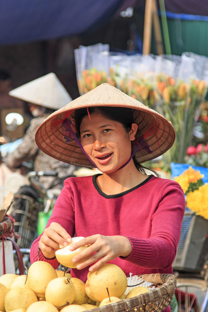 hat, real people, looking at camera, market vendor, fruit, portrait, holding, market, smiling, one person, food and drink, outdoors, casual clothing, happiness, freshness, healthy eating, day, focus on foreground, cheerful, food, lifestyles, young adult, people