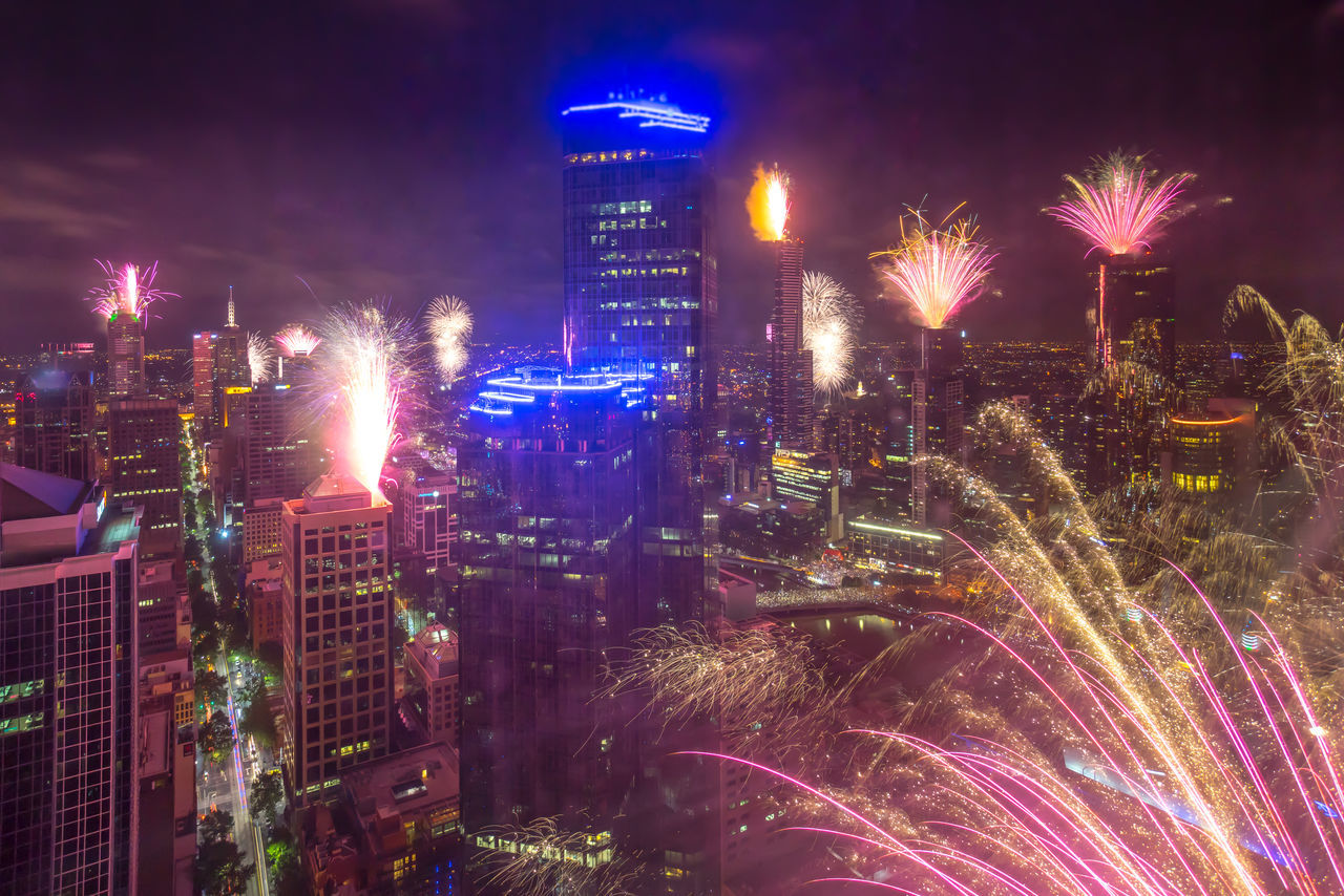 illuminated, building exterior, architecture, night, city, cityscape, long exposure, built structure, firework display, celebration, motion, firework - man made object, no people, outdoors, skyscraper, sky