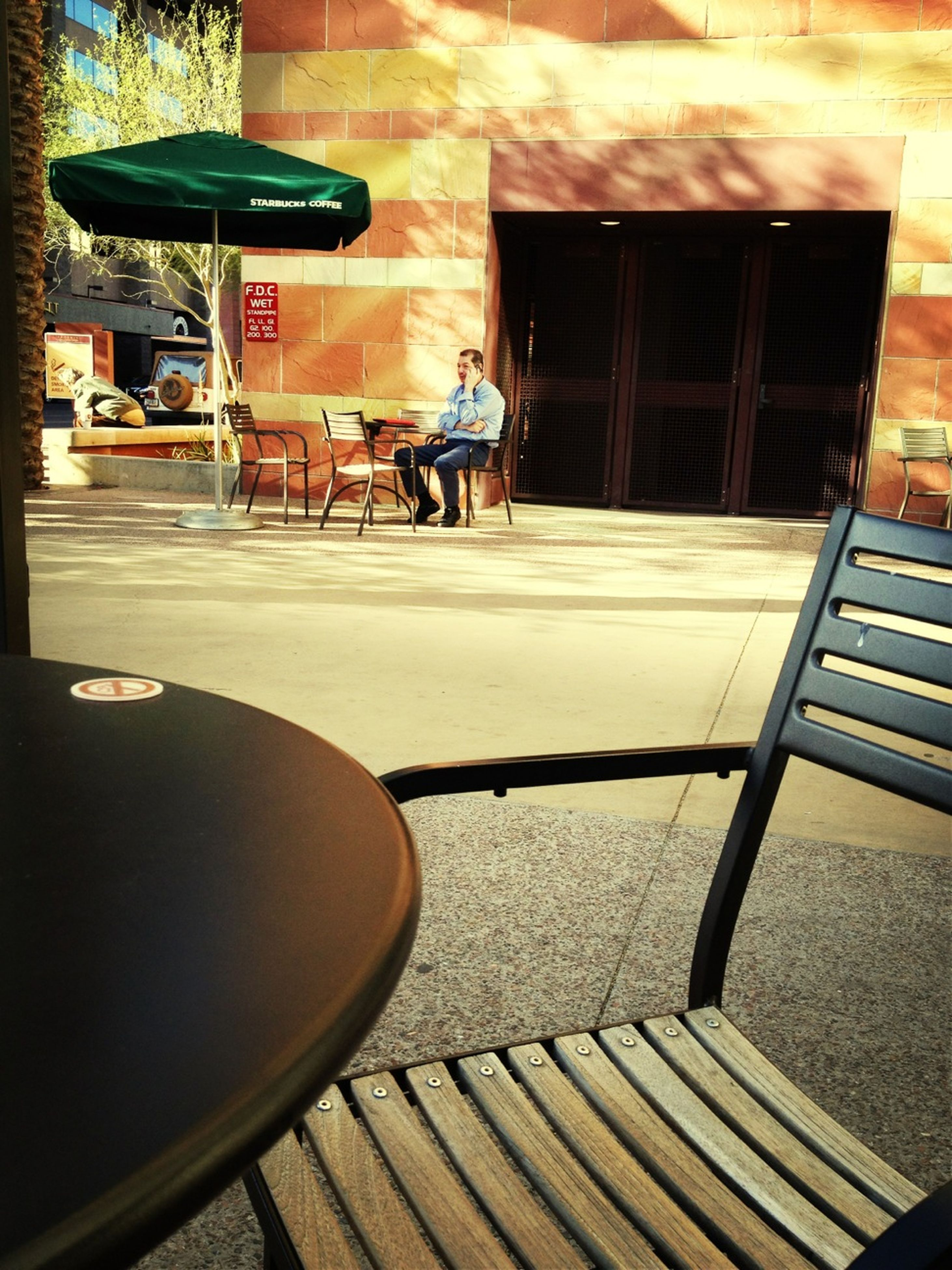 architecture, building exterior, built structure, chair, city, sunlight, street, table, empty, absence, shadow, building, day, sidewalk cafe, outdoors, incidental people, no people, restaurant, sidewalk, high angle view