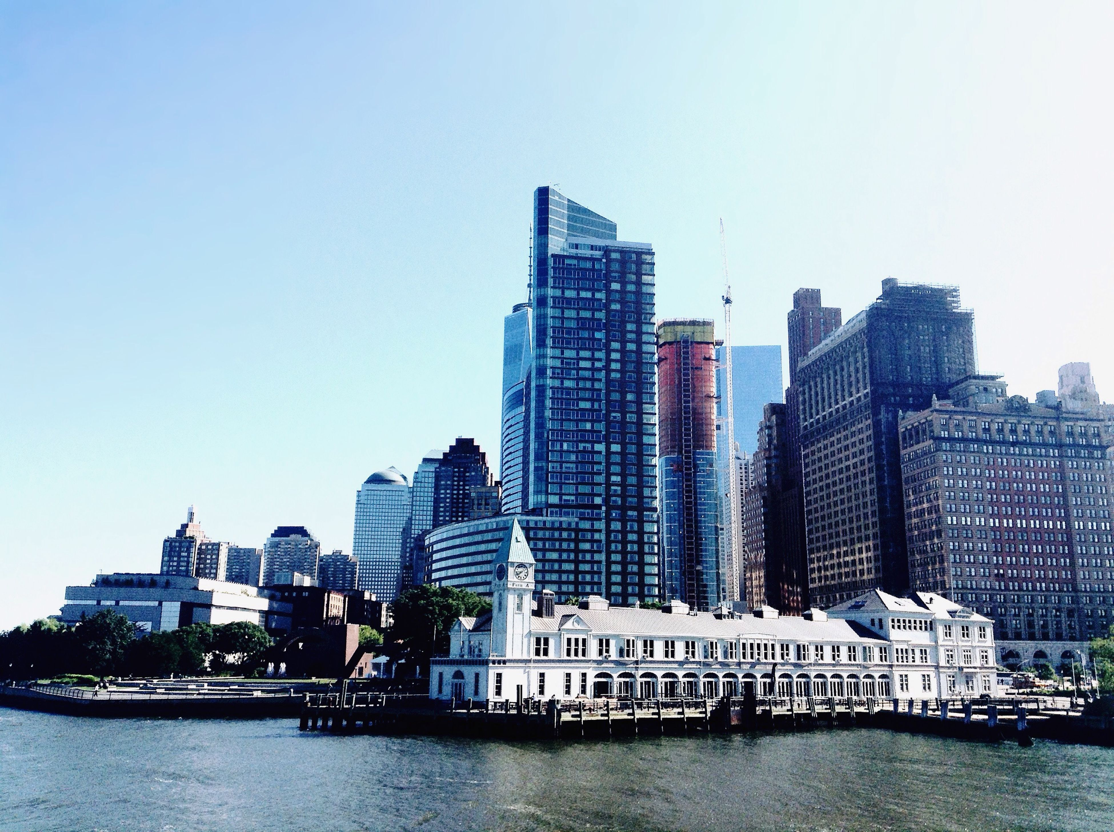 building exterior, waterfront, architecture, water, clear sky, built structure, city, skyscraper, copy space, cityscape, urban skyline, office building, river, modern, tall - high, nautical vessel, tower, sea, financial district, skyline