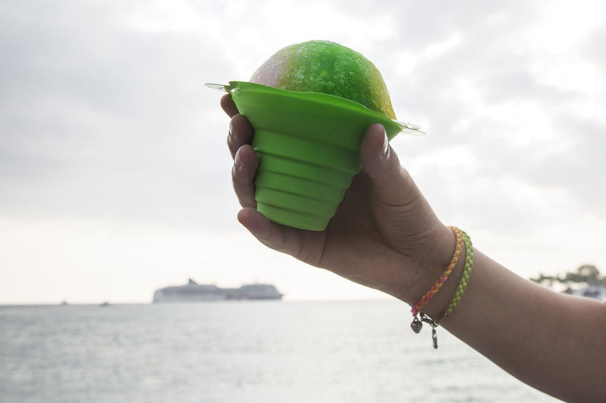 Girl is Holding Ice cream - cruise ship in the background Cruise Ship Green Beachside Close-up Cloud - Sky Day Focus On Foreground Food Food And Drink Freshness Fruit Green Color Holding Human Body Part Human Hand Leisure Activity Lifestyles Nature One Person Outdoors Real People Shave Ice Sky Sweet Water