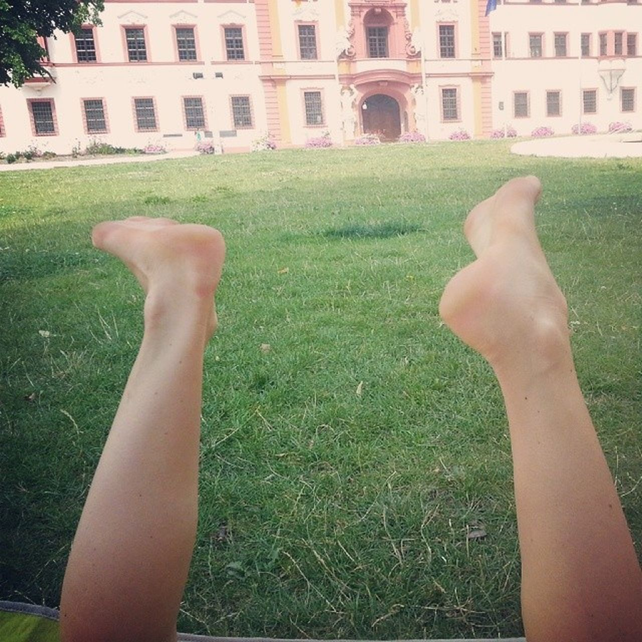grass, real people, one person, personal perspective, human leg, human body part, building exterior, architecture, leisure activity, outdoors, lifestyles, day, lawn, low section, women, built structure, human hand, close-up, people