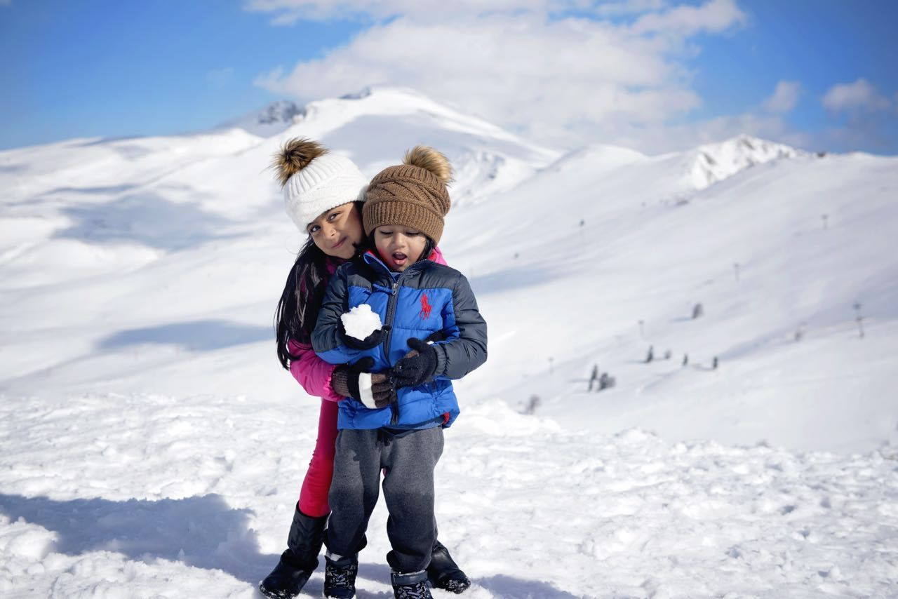 snow, winter, cold temperature, mountain, togetherness, real people, full length, nature, leisure activity, childhood, beauty in nature, day, warm clothing, outdoors, love, bonding, family with one child, sky, vacations, sunlight, girls, son, lifestyles, mountain range, boys, happiness, looking at camera, scenics, adventure