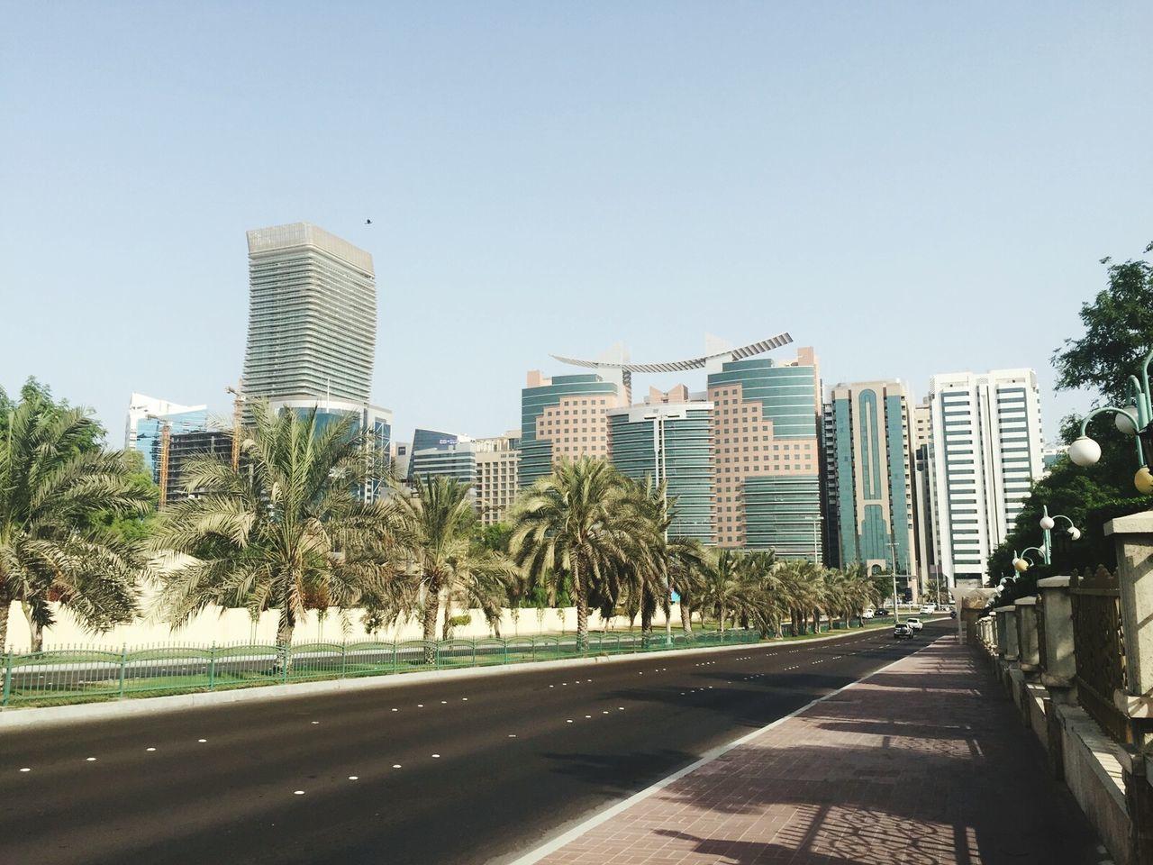Empty Road Leading Towards Buildings In City