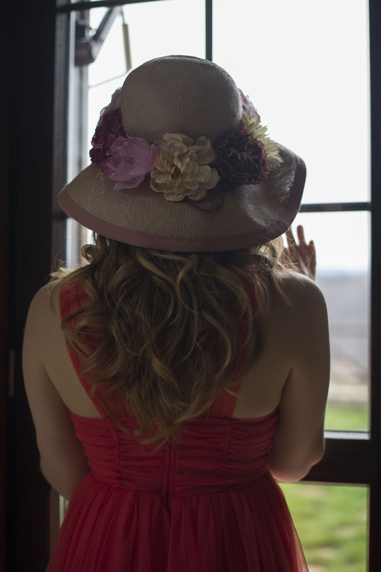 Back To Camera Blonde Decorated Hanging Lamps Flower Inside Looking Outside Red Dress Waiting Window Woman
