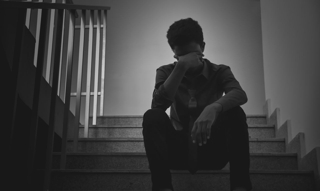 Low Angle View Of Depressed Man Sitting On Steps
